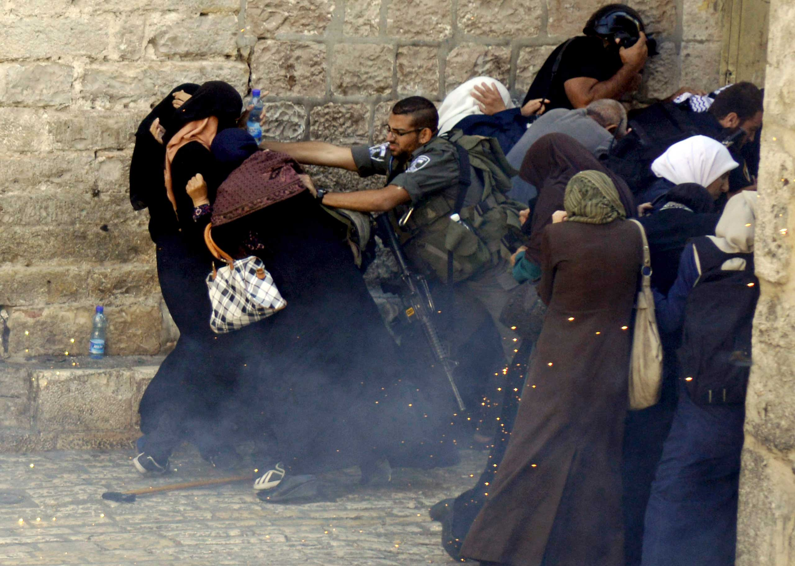 Israeli border policeman push Palestinian women during clashes in the Old City of Jerusalem, Oct. 13, 2014.