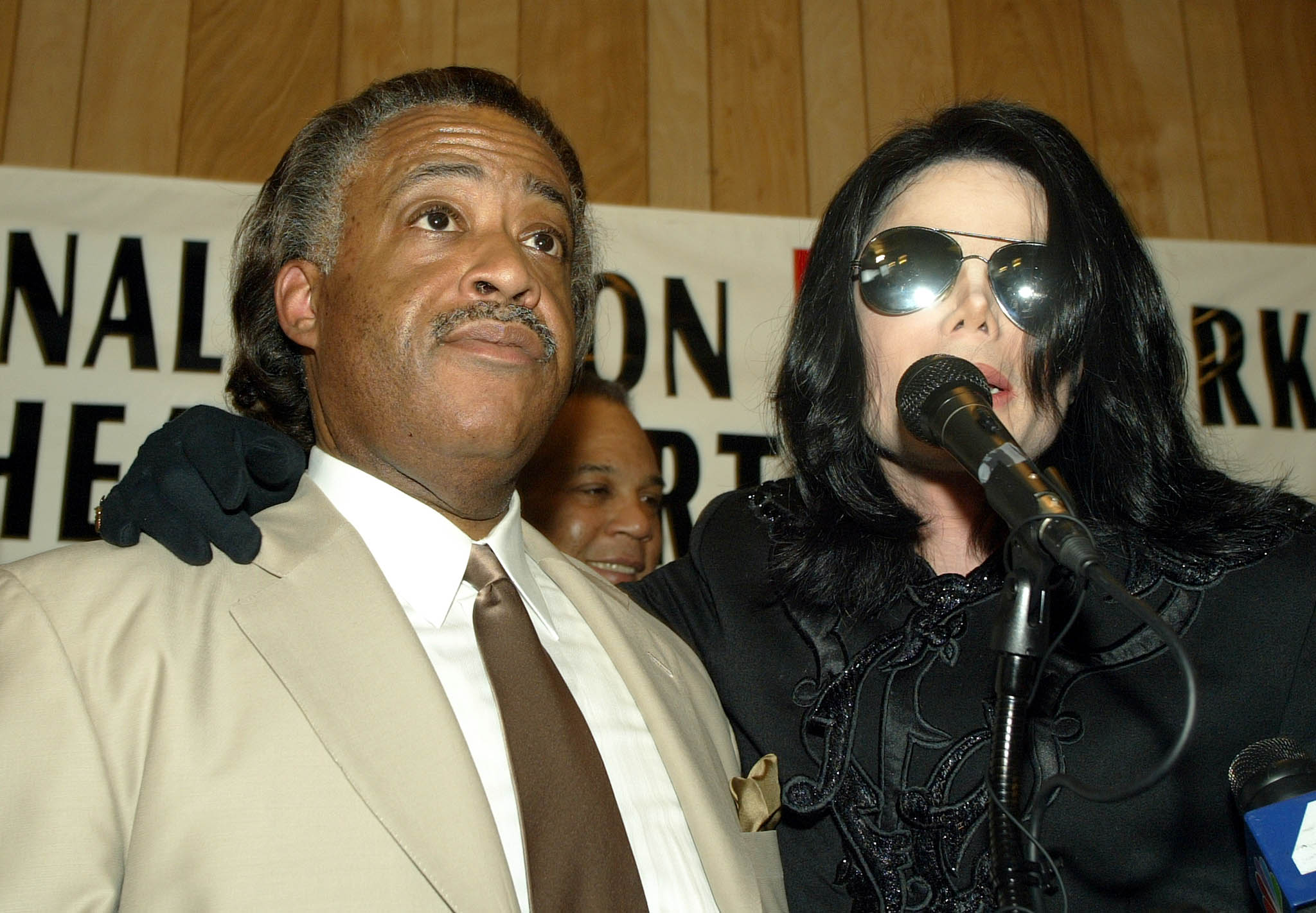 Musician Michael Jackson (R) stands with Rev. Al Sharpton at Sharpton's National Action Network headquarters  in the Harlem neighborhood of New York City on July 6, 2002.