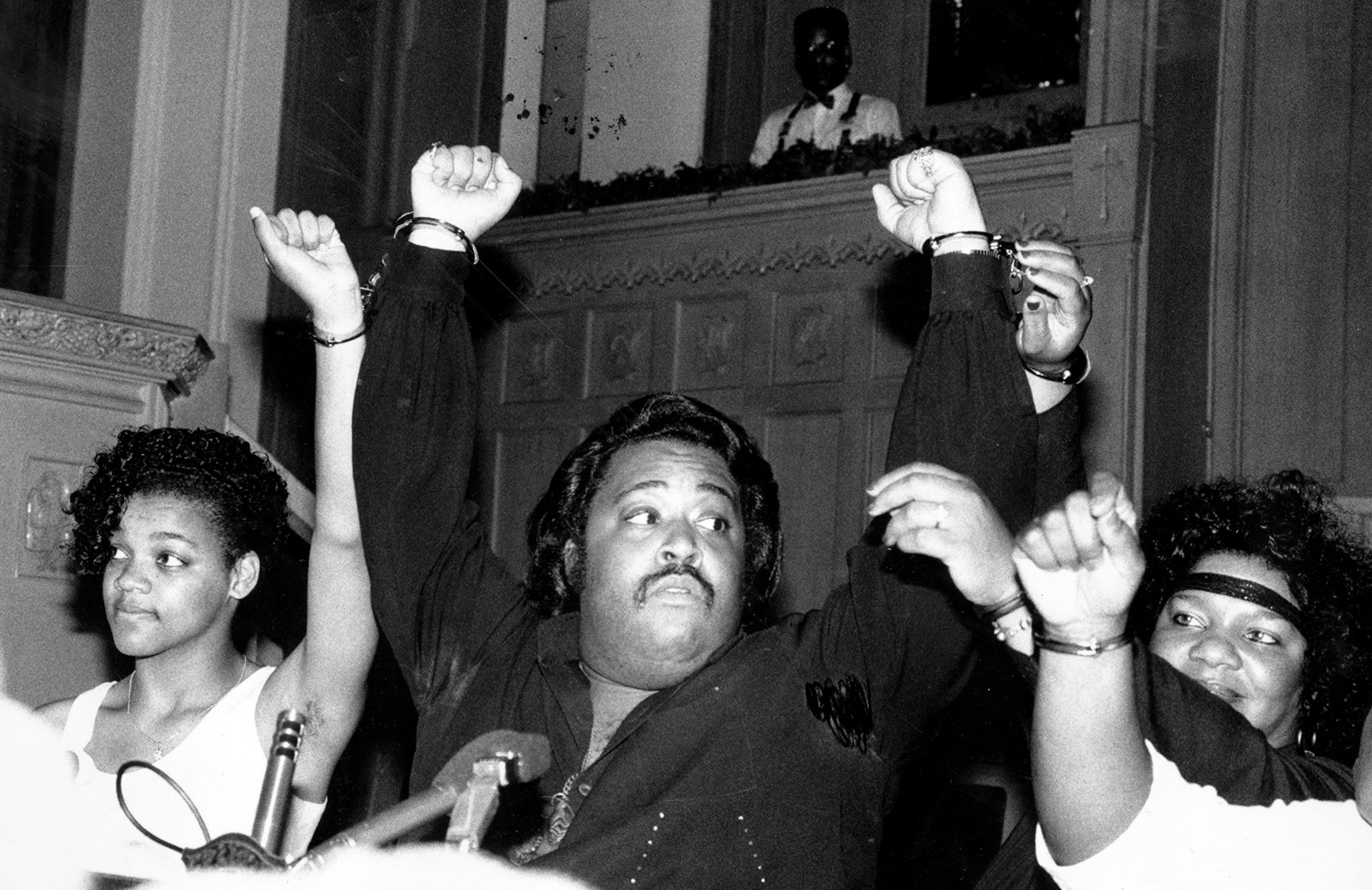From left: Tawana Brawley, the Rev. Al Sharpton, and Glenda Brawley are handcuffed to one another as they prepare to leave church for a bus trip to Democratic Convention in Atlanta, July 16, 1988.