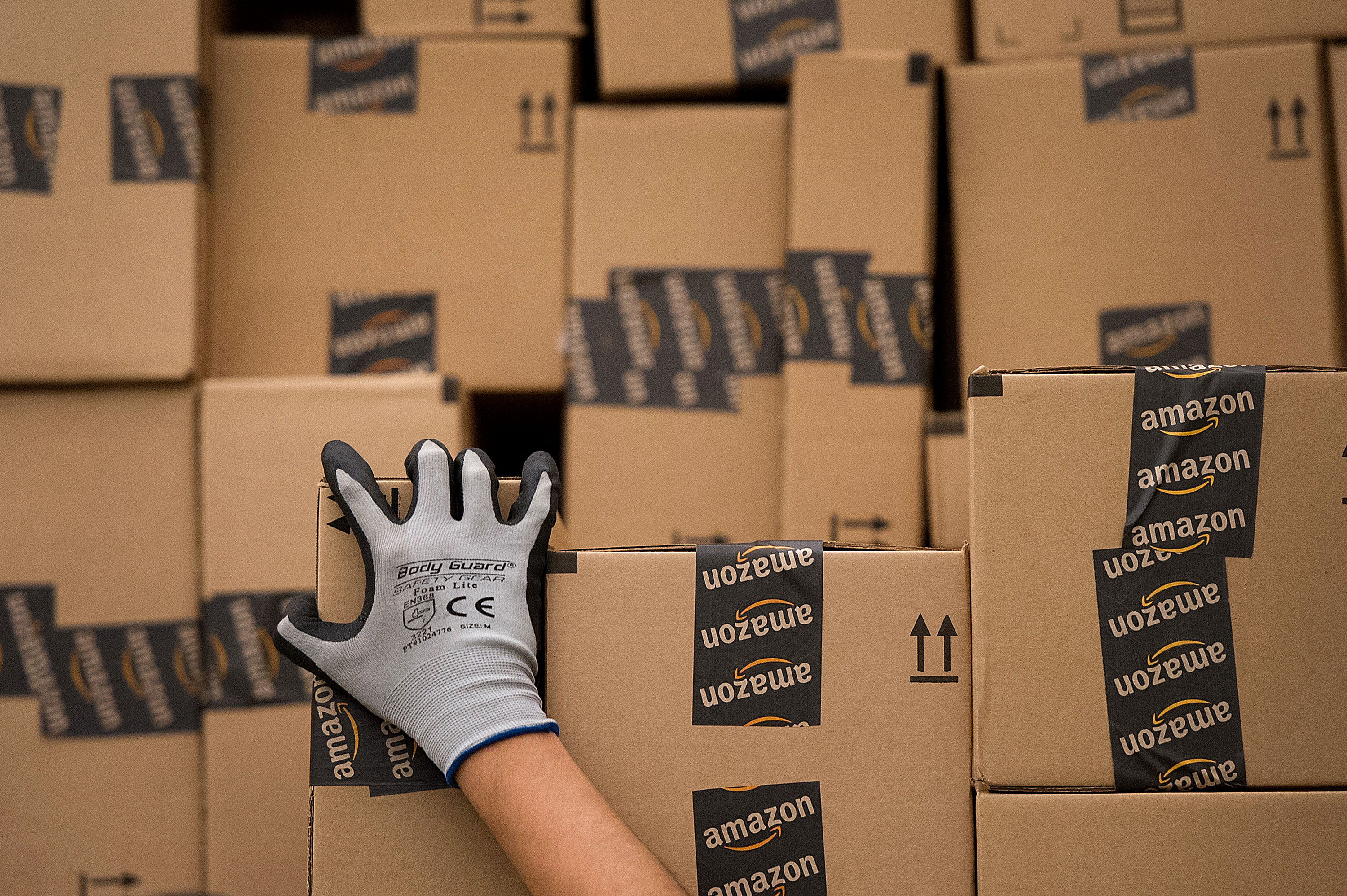 An employee loads a truck with boxes to be shipped at the Amazon.com Inc. distribution center in Phoenix, Arizona, U.S. on Monday, Nov. 26, 2012.