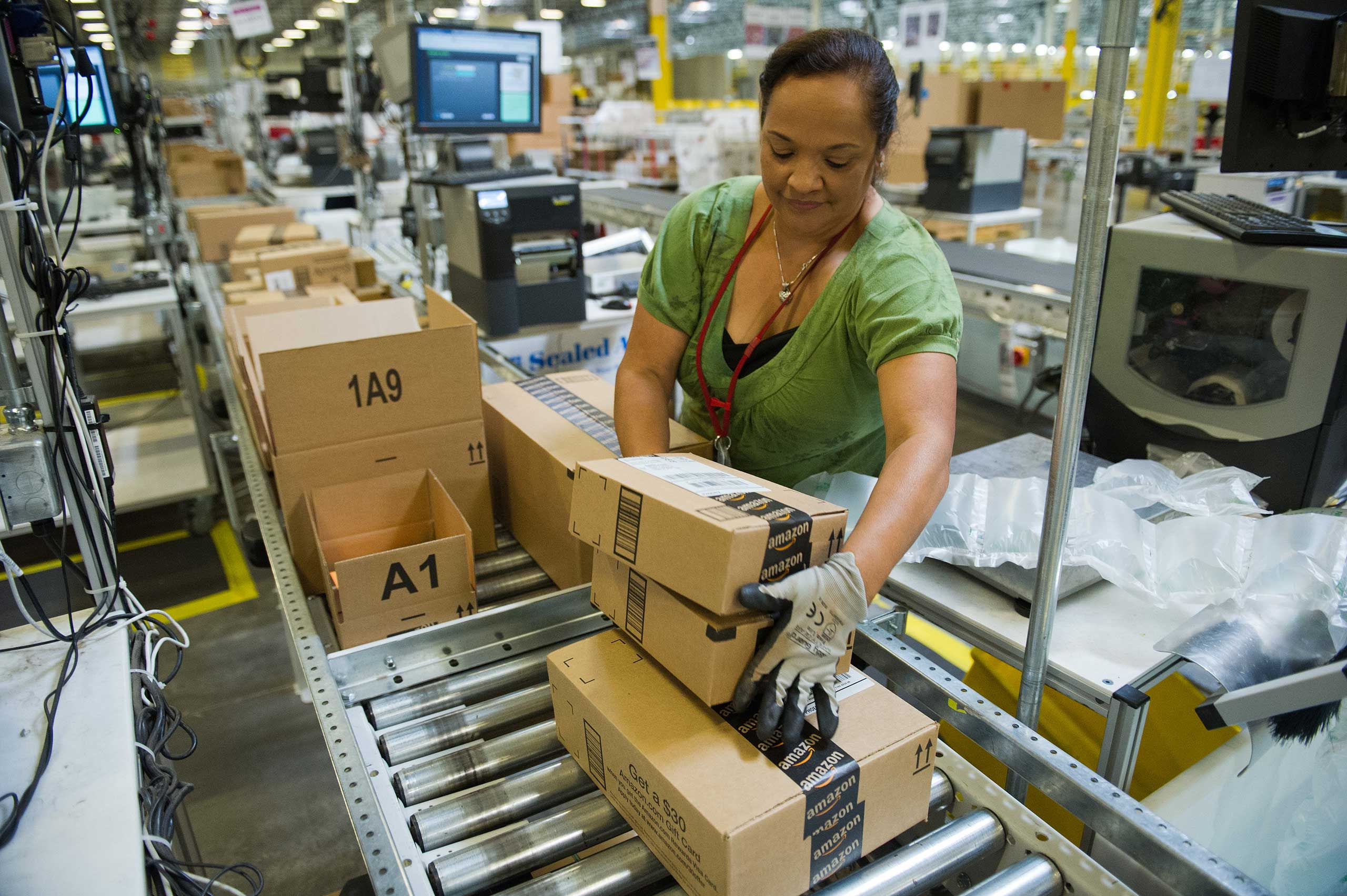 Employee Maria Miller loads boxes onto a conveyer belt for shipping at the Amazon.com Inc. distribution center in Phoenix, Arizona, U.S. on Monday, Nov. 26, 2012.