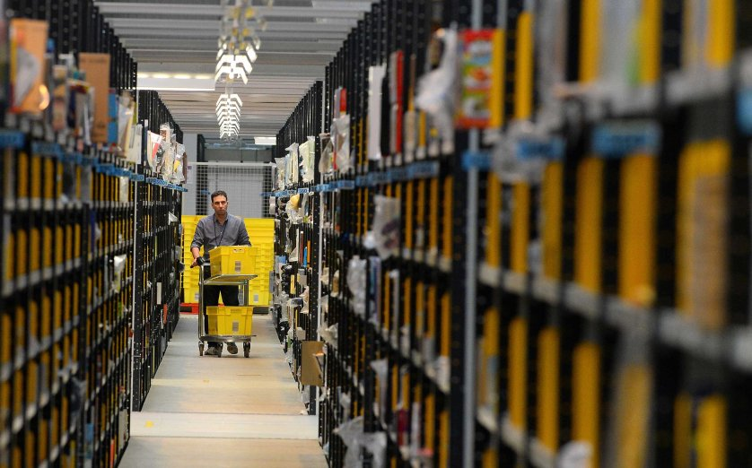 A worker collects order items at the Fulfilment Centre for online retail giant Amazon in Peterborough, central England, on Nov. 28, 2013.