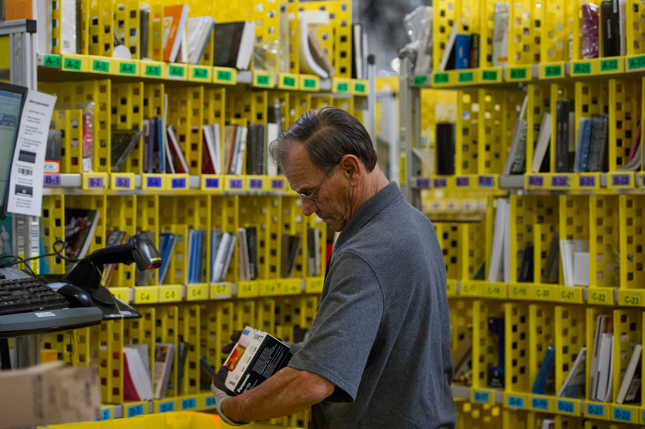 An employee packs merchandise for shipment at the Amazon.com Inc. fulfillment center in Phoenix, Arizona, Dec. 2, 2013.