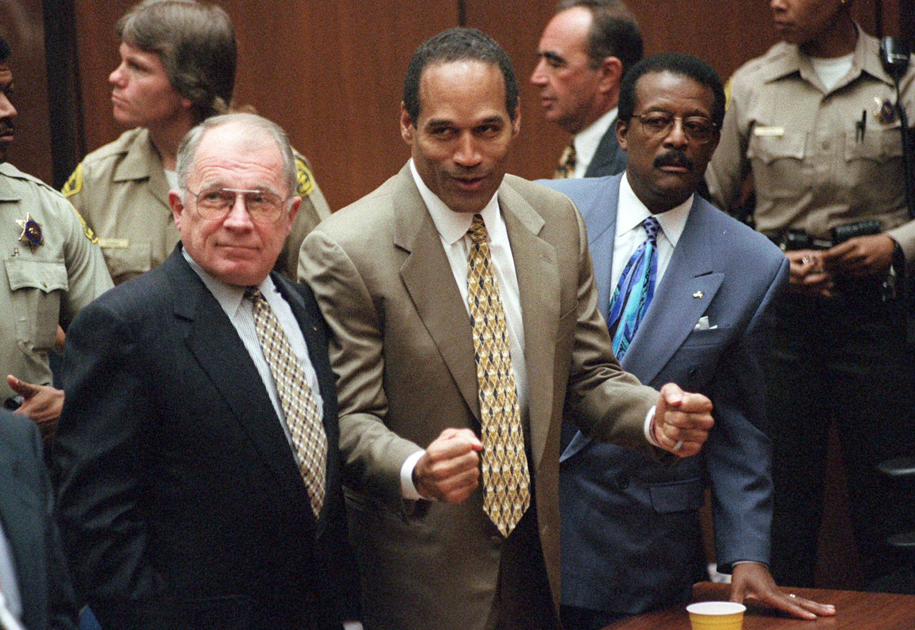 O.J. Simpson reacts as he is found not guilty of murdering his ex-wife Nicole Brown Simpson and her friend Ron Goldman, at the Criminal Courts Building in Los Angeles. At left is defense lawyer F. Lee Bailey and at right is defense attorney Johnnie Cochran Jr. Defense attorney Robert Shapiro is in profile behind them. (AP Photo/Daily News, Myung J. Chun, Pool, File)