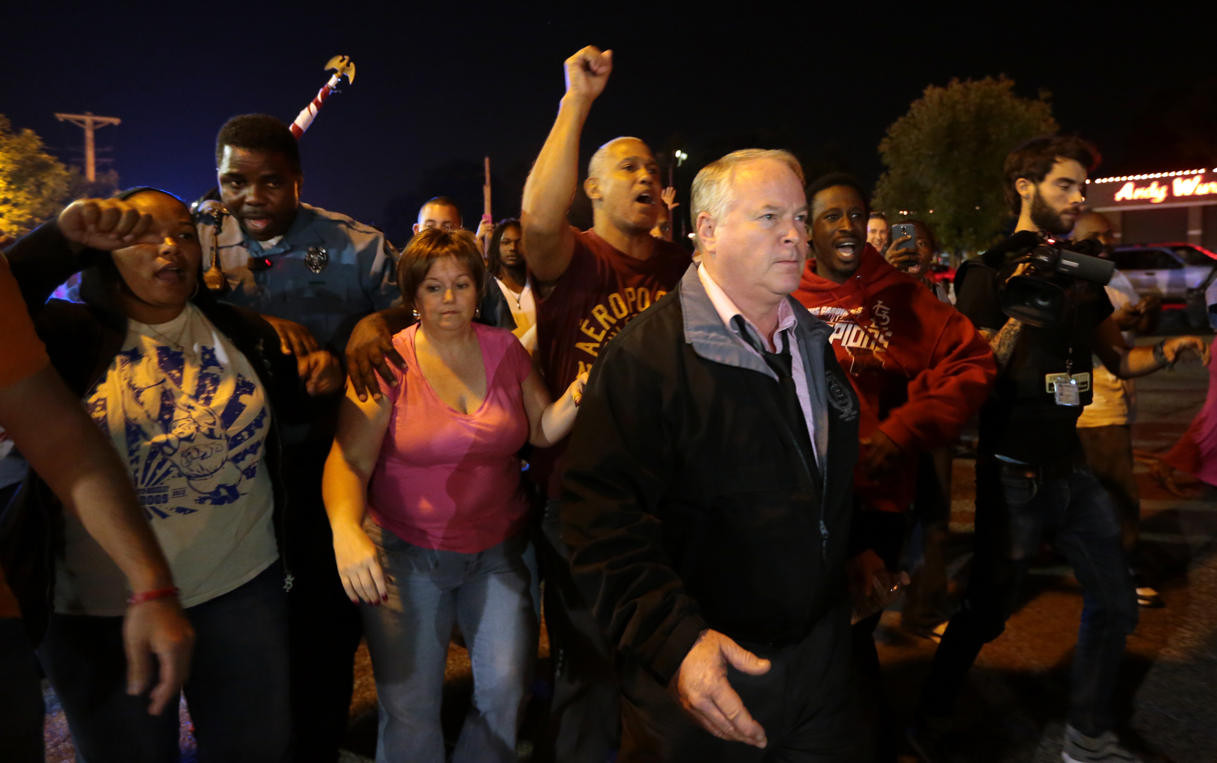 Ferguson Police Chief Tom Jackson begins to march with protesters before clashes led to arrests in front of the Ferguson Police Department, on Thursday, Sept. 25, 2014.