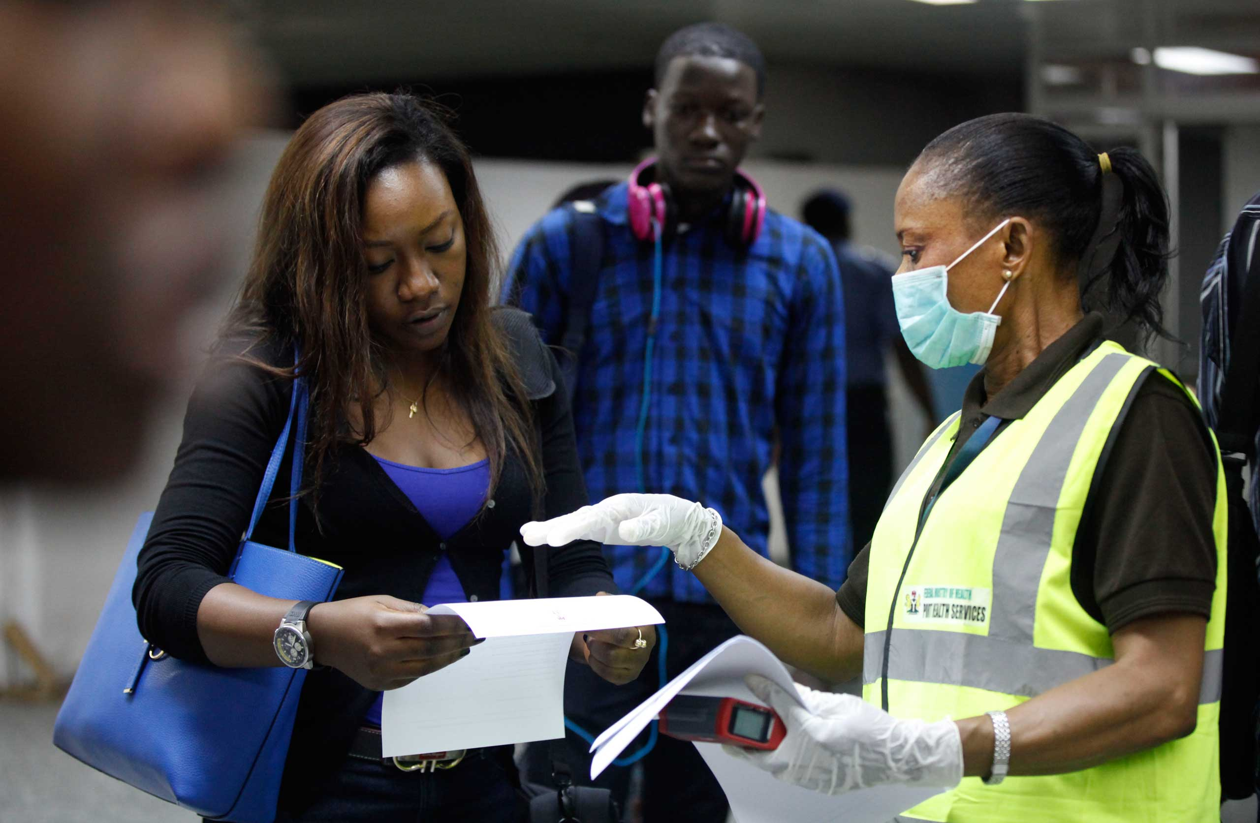 A Nigerian port health official speaks to a passenger at the arrivals hall of Murtala Muhammed International Airport in Lagos, Nigeria, Aug. 6, 2014.