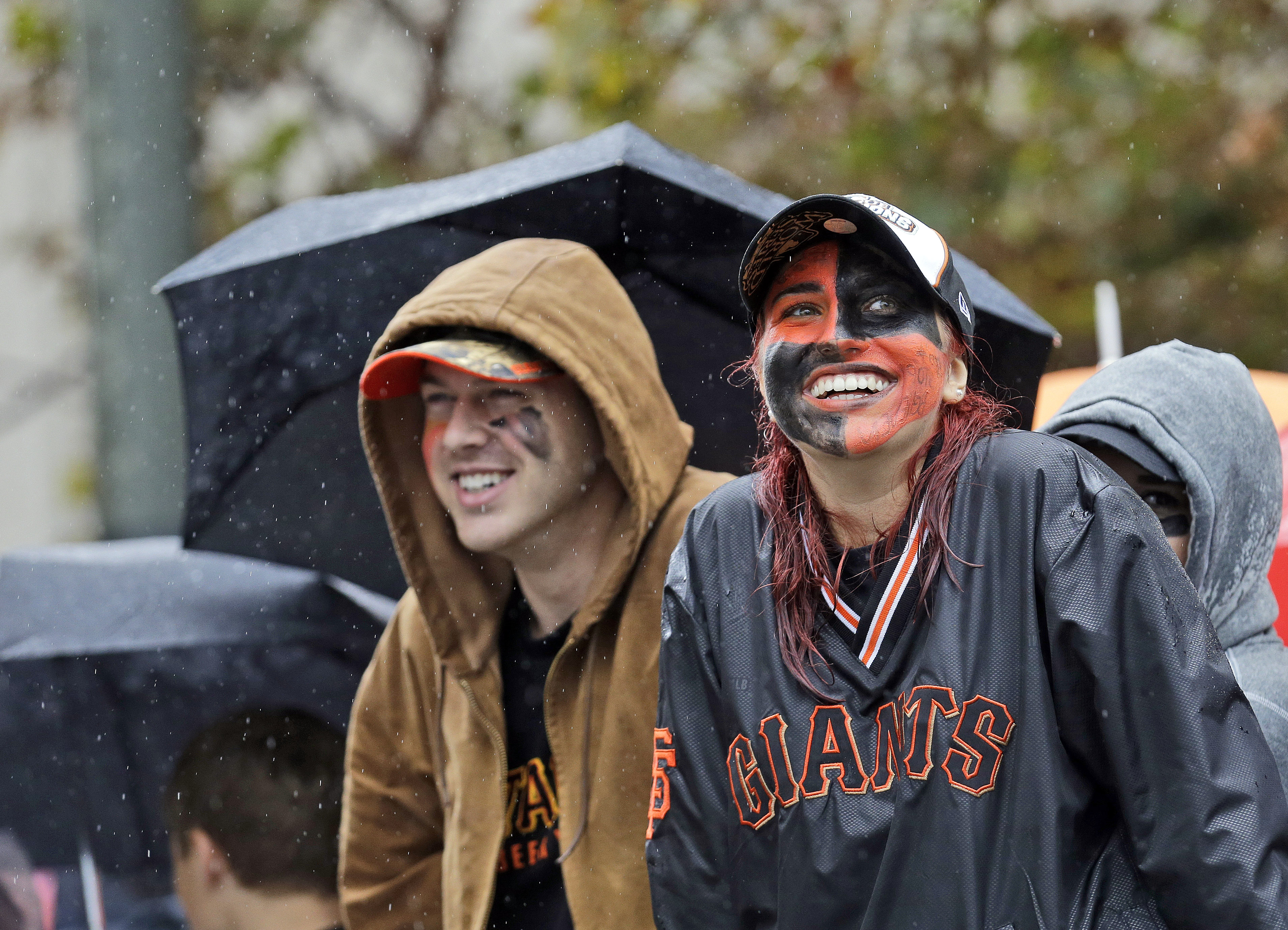 San Francisco Giants baseball fans Megan McPhillips, right, and Travis Saracco from Santa Rosa, Calif., wait in the rain for the start of the victory parade for the 2014 World Series Champion San Francisco Giants on Friday, Oct. 31, 2014 in San Francisco.