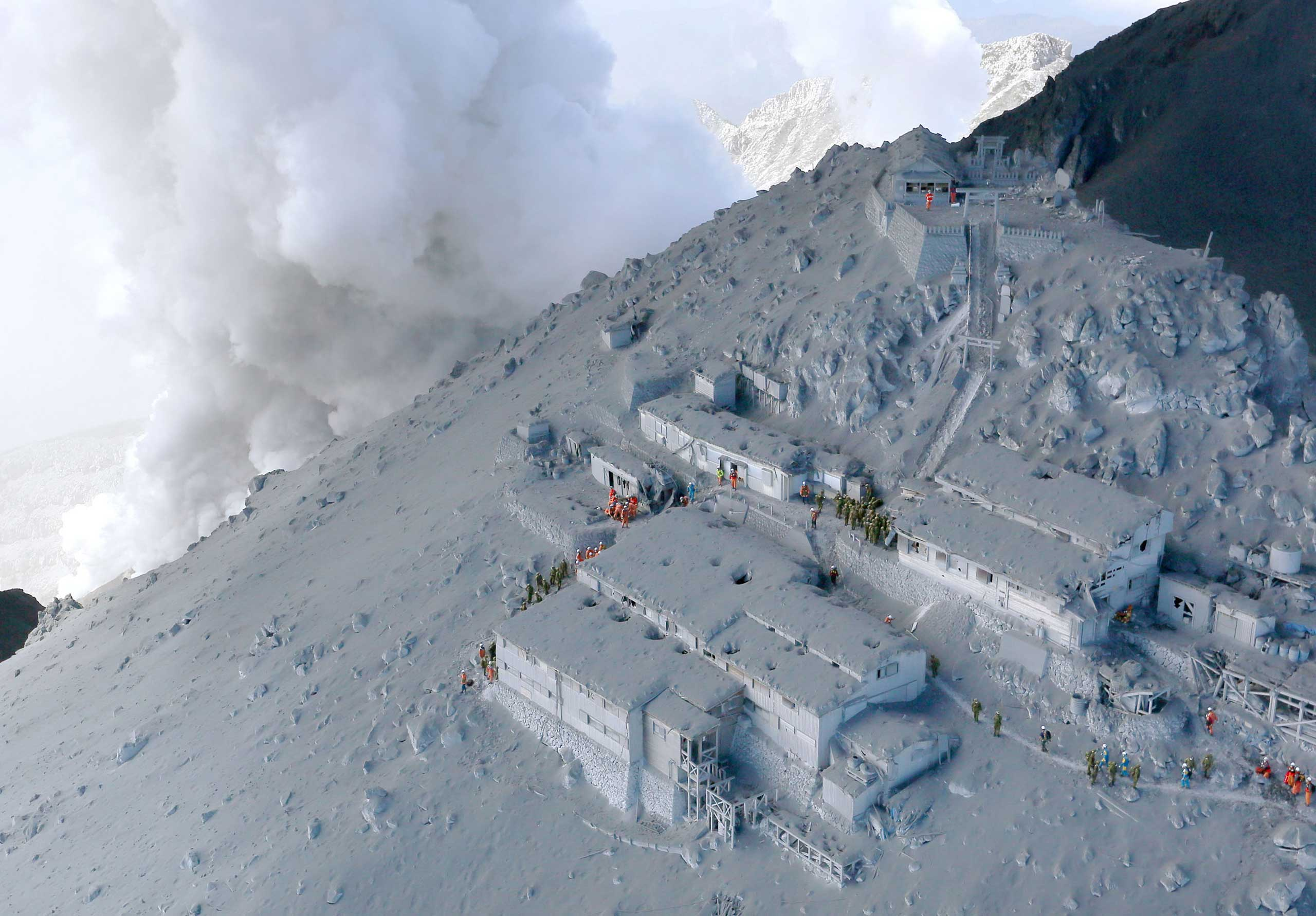 Sept. 28, 2014. Firefighters and members of Japan's Self-Defense Forces conduct a rescue operation at a cabin near the peak of Mount Ontake as plumes of smoke billow in central Japan.
