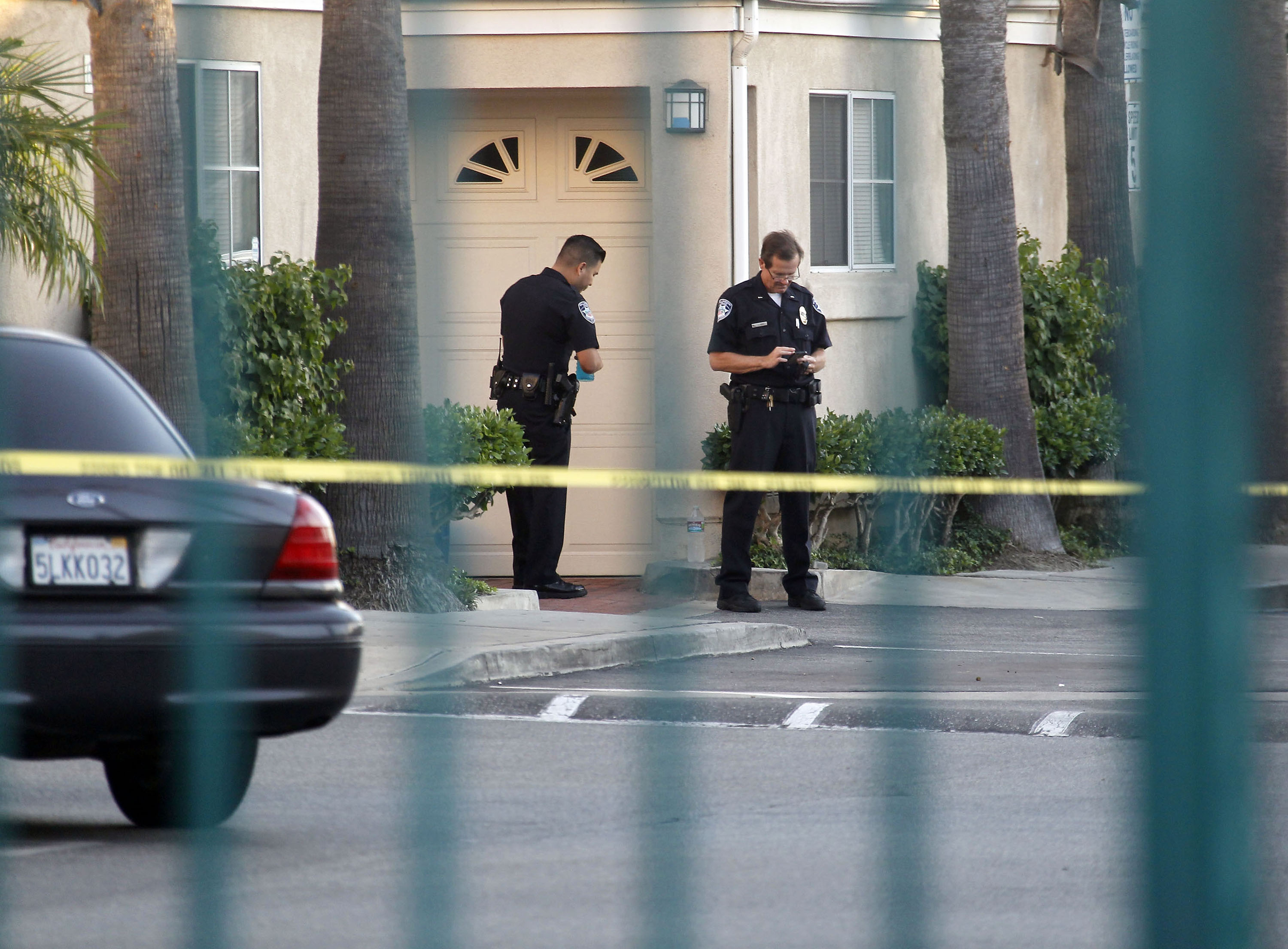 Police officers stand by the scene of a shooting in Bell Gardens, Calif., on Sept. 30, 2014