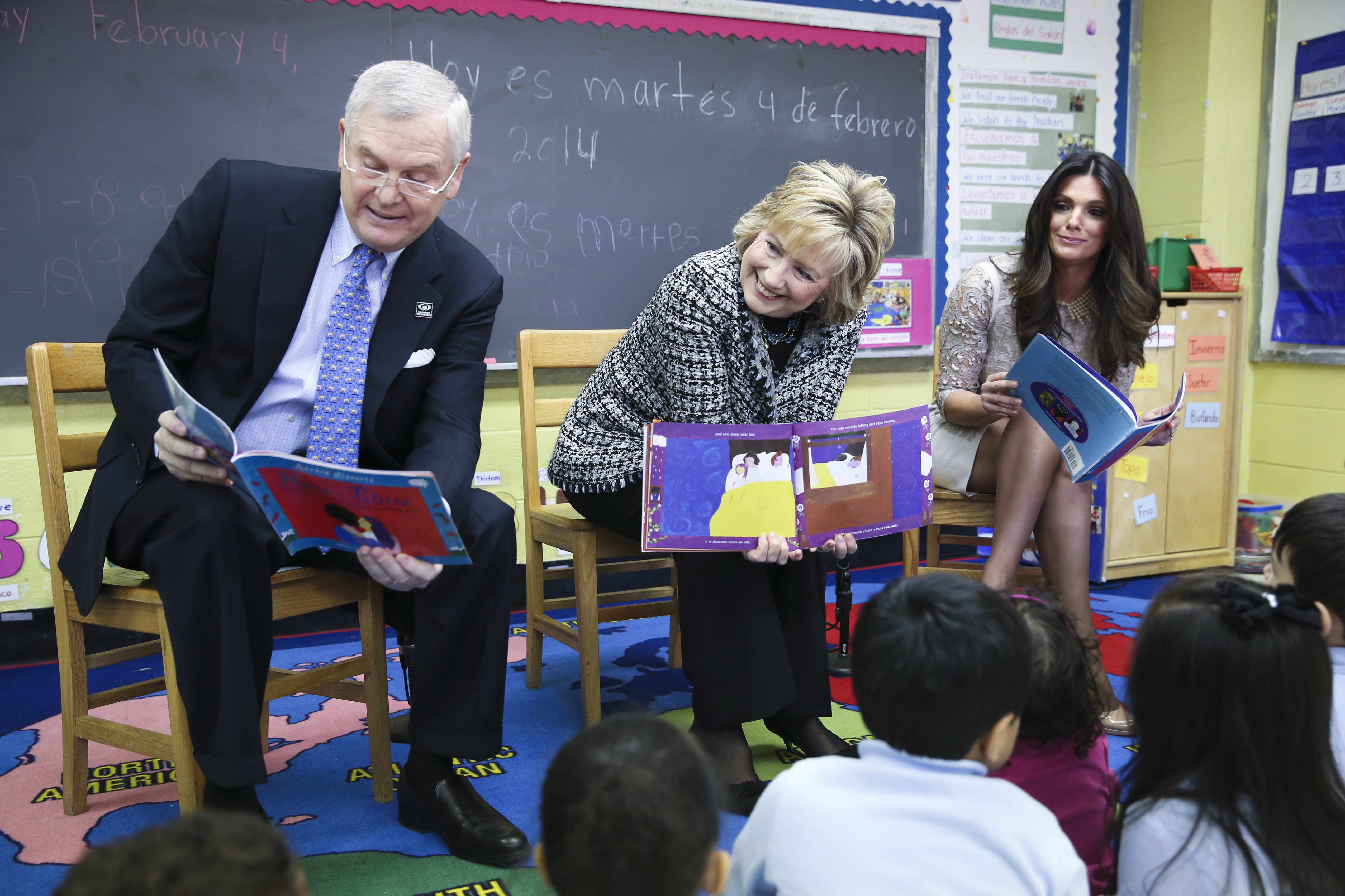 Hillary Rodham Clinton, center, alongside Randy Falco, president and CEO of Univision Communications Inc, left, and Barbara Bermudo, host of Univision's news magazine program  Primer Impacto , right, read to children at the launch of  Pequeños y Valiosos  (Young and Valuable), a parent-focused effort on early childhood development, at the East Harlem Council for Human Services Bilingual Headstart Program, Tuesday, Feb. 4, 2014, in New York.