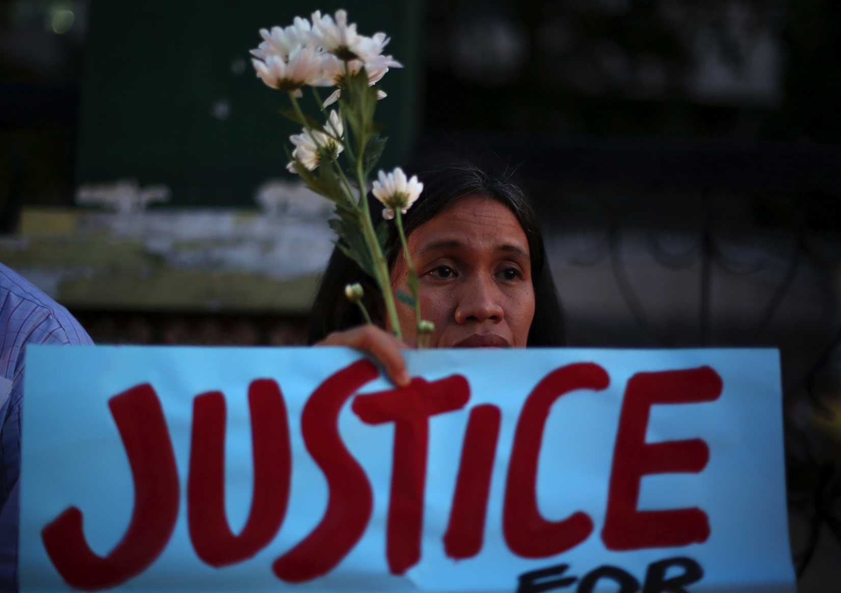 A Filipino activist holds flowers and a slogan during prayers in suburban Quezon city, Philippines on Thursday Oct. 23, 2014, to call for justice for the killing of Filipino transgender Jeffrey  Jennifer  Laude.