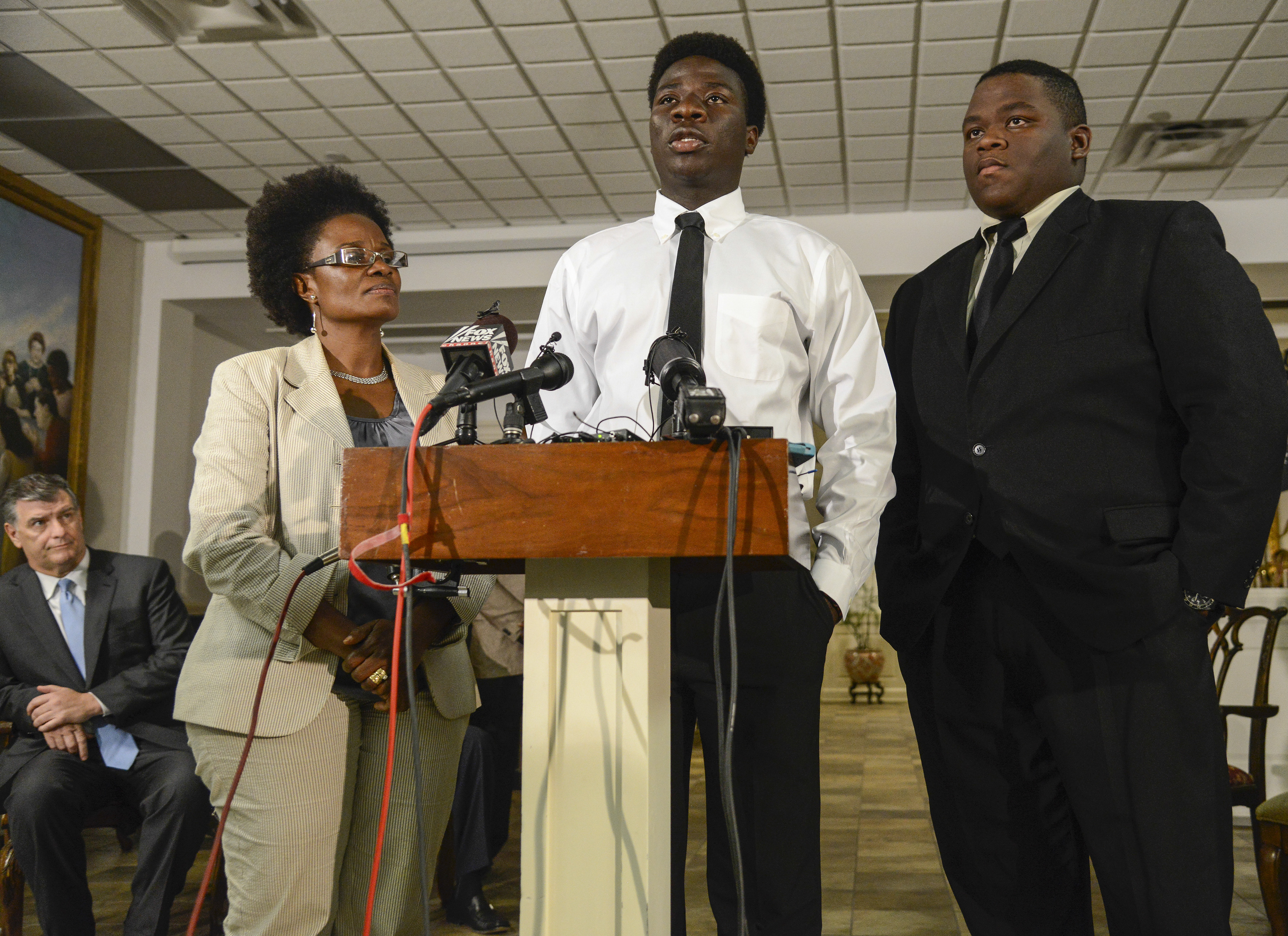 Karsiah Duncan, center, son of Ebola patient Thomas Eric Duncan speaks during a news conference while Dallas Mayor Mike Rawlings, left rear, and Saymendy Lloyd look on, Tuesday, Oct. 7, 2014, in Dallas.