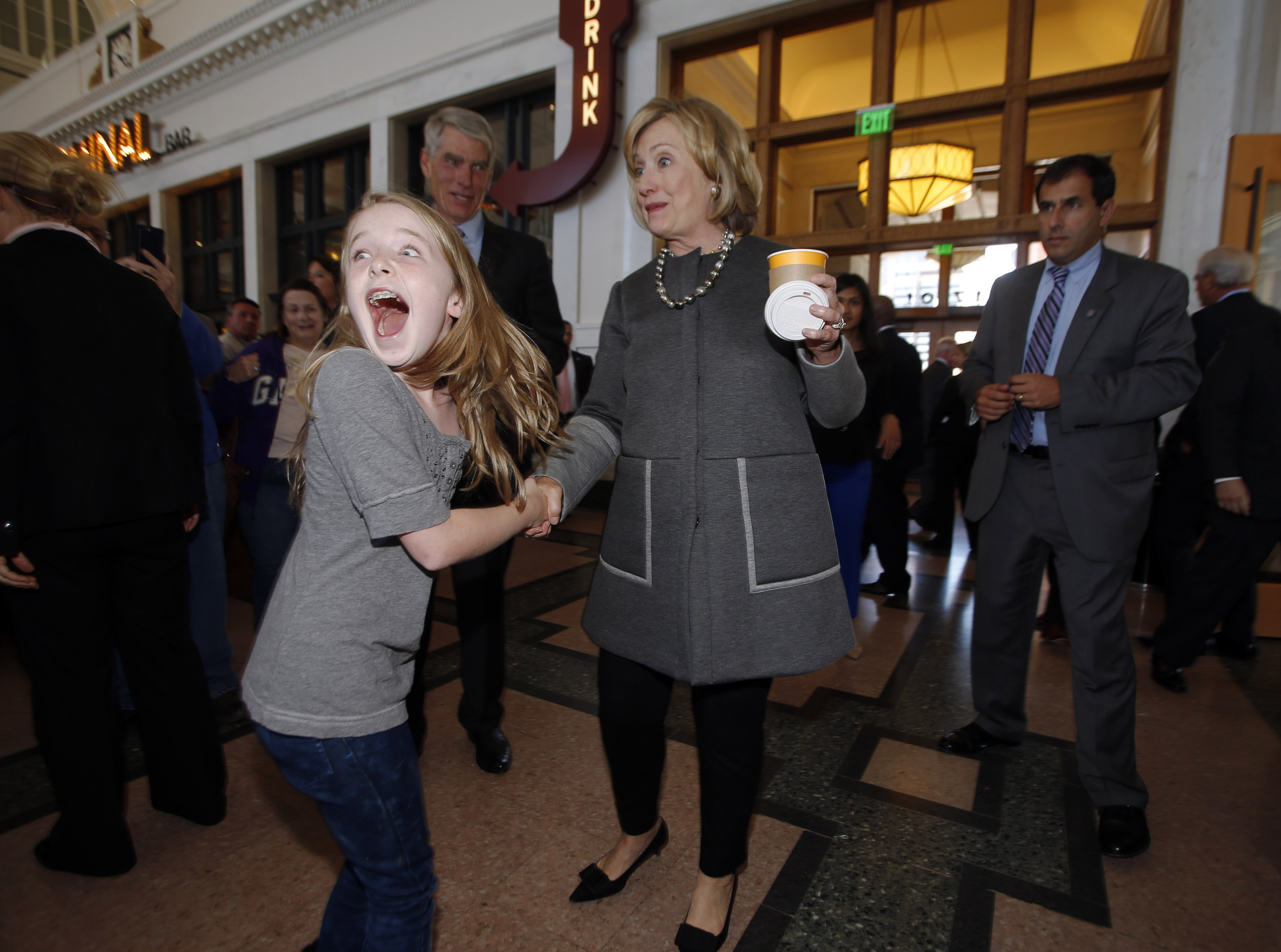 Ten-year-old Macy Friday, front left, reacts as she looks back at her family after meeting Hillary Clinton, front right, as she campaigns for U.S. Sen. Mark Udall, D-Colo., back, during a stop in Denver on Monday, Oct. 13, 2014.