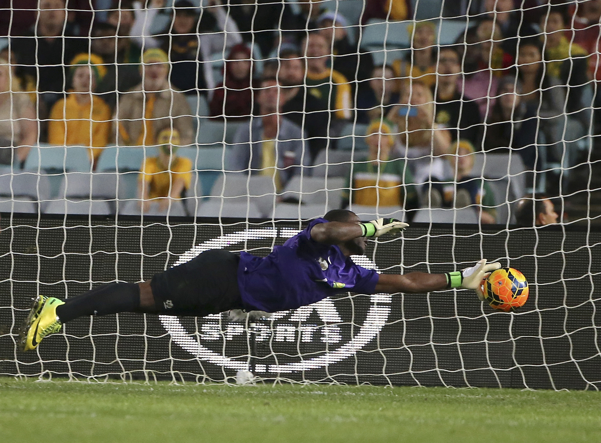 In this file photo dated May 26, 2014, South Africa's goalkeeper Senzo Meyiwa makes a diving save against Australia during their friendly soccer match in Sydney