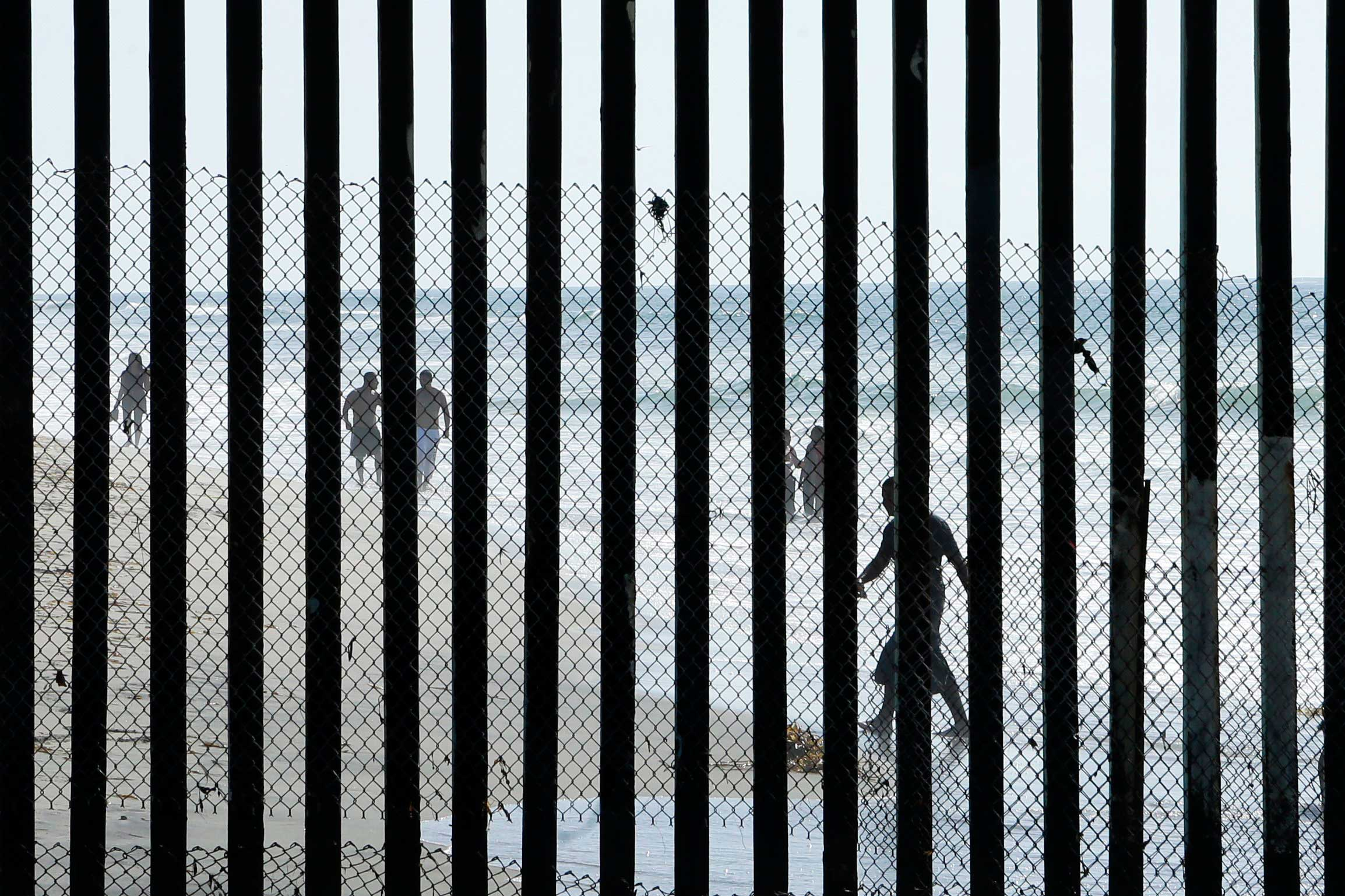 Oct. 29, 2014. People walk along the beach in Tijuana, Mexico, where metal bars marking the border with the U.S. meet the sea as seen from San Diego.