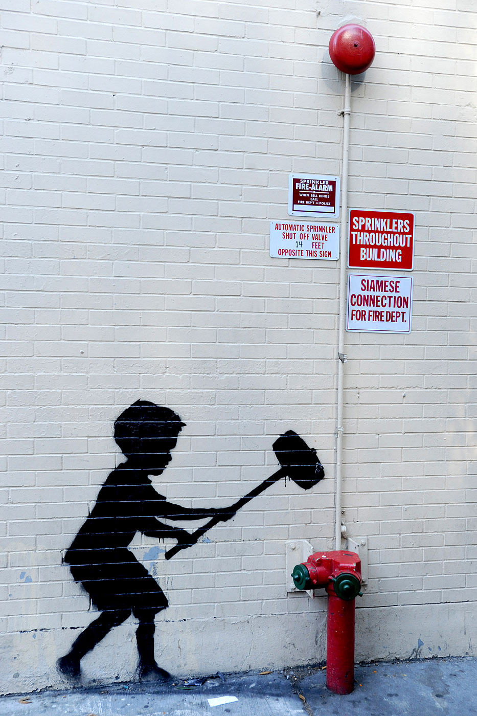 A Banksy depicting a silhouette of a hammer boy playing 'strong man' in the Upper West Side of new York City, October 20, 2013.