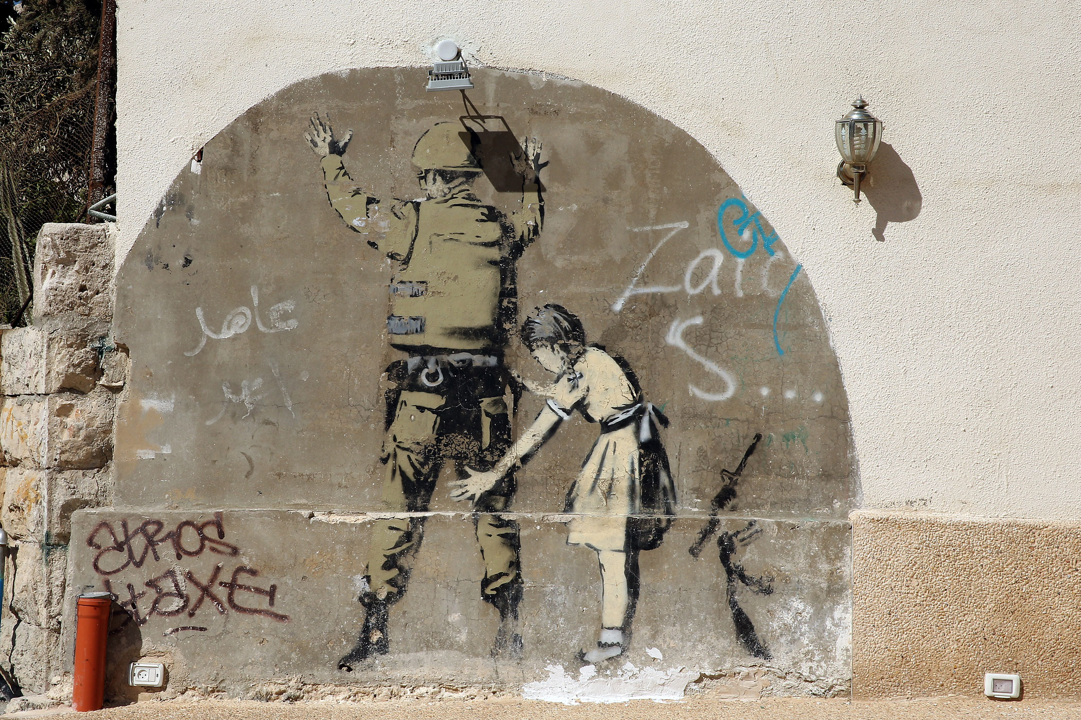 A Banksy wall painting seen on the apartheid wall near Bethlehem on June 16, 2013 in central West Bank, Palestine.