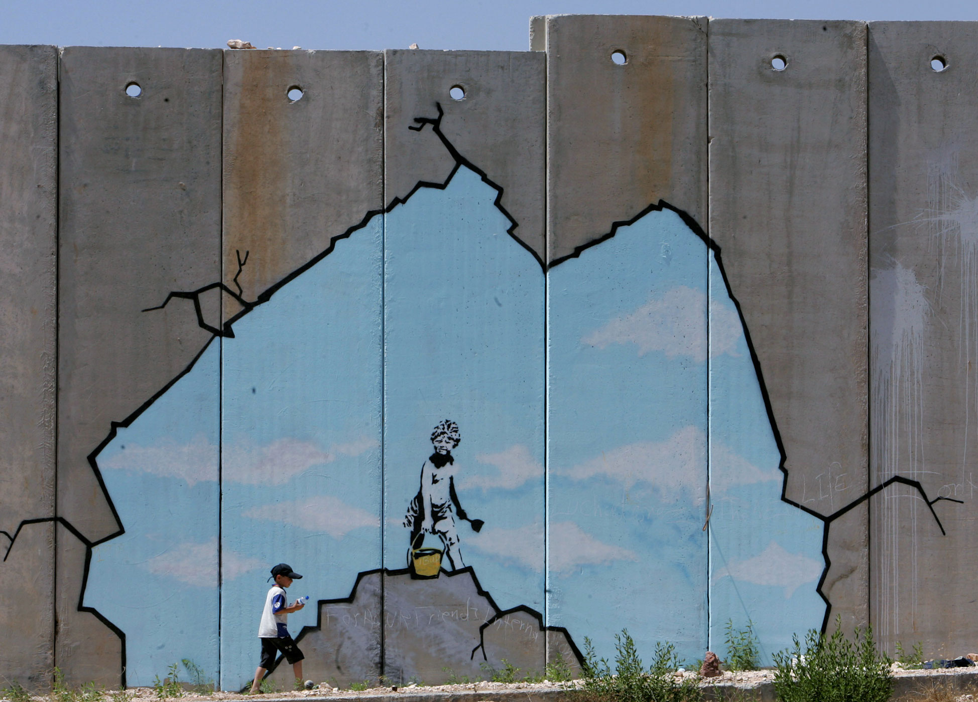 A Palestinian boy walks past a work by Banksy near the Kalandia checkpoint in the West Bank on August 10, 2005.