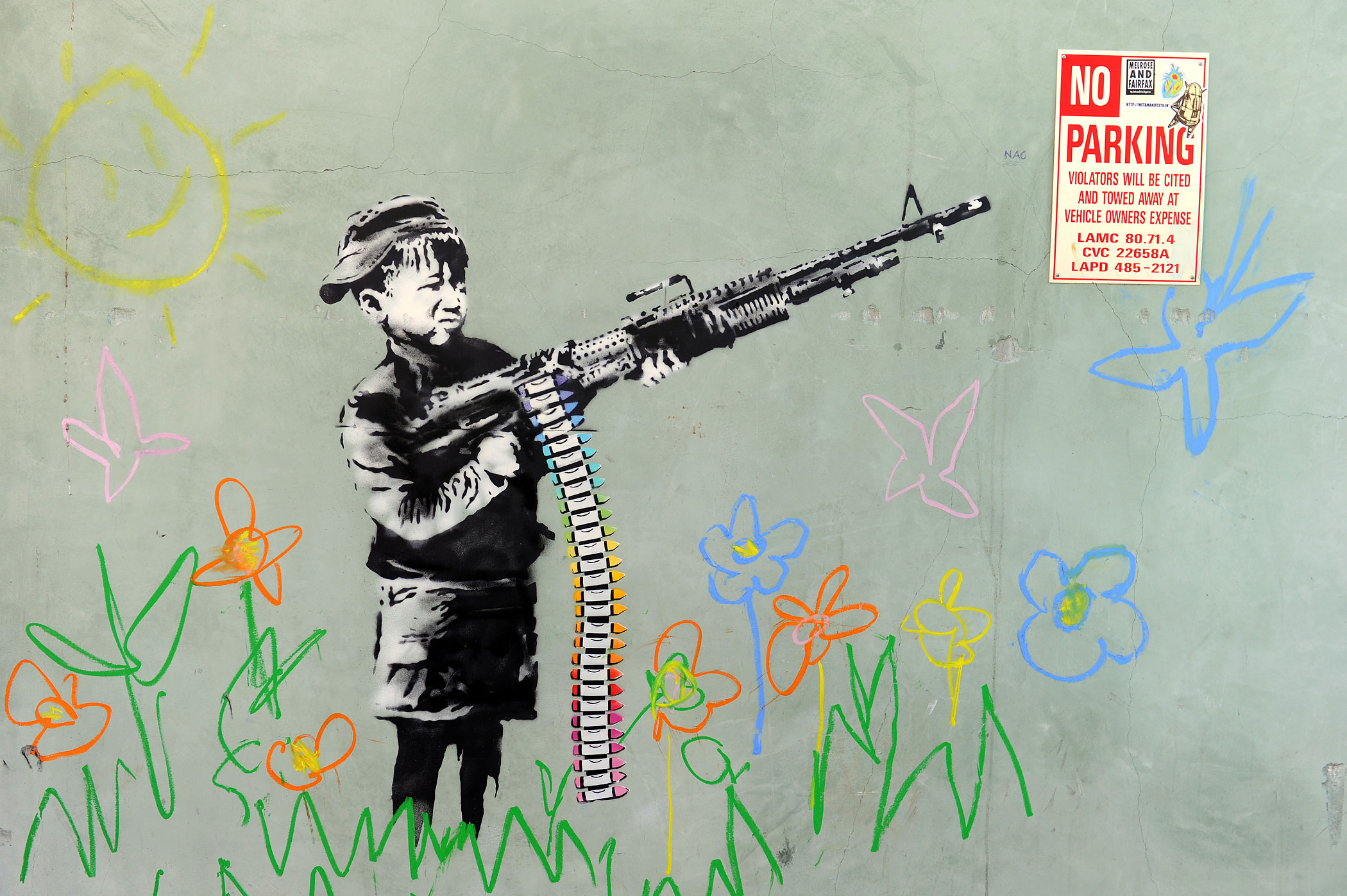 A Banksy depicting a child wielding a machine gun, in black and white surrounded by colored flowers, is spotted in Westwood, Ca. on February 17, 2011.