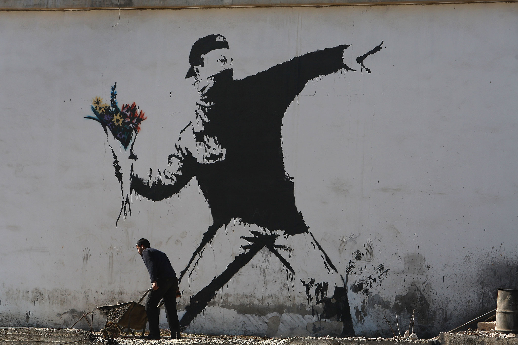 A Palestinian laborer works under a large wall painting by Banksy on December 5, 2007 in Bethlehem in the West Bank.