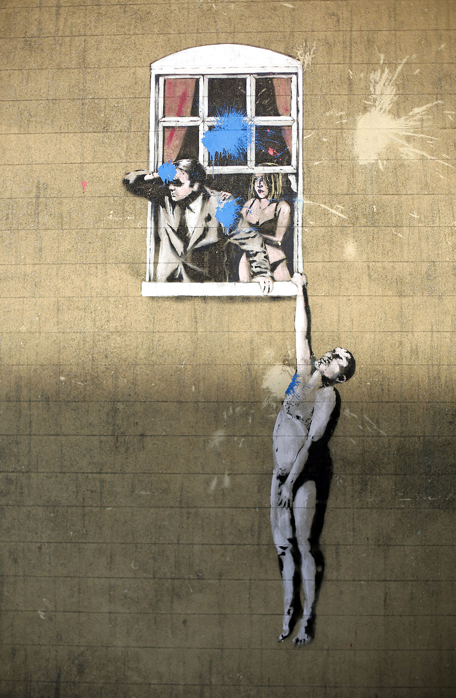 A mural by Banksy, which has been defaced by blue paint bombs, is seen on the side of a building in Park Street on March 4, 2013 in Bristol, England.