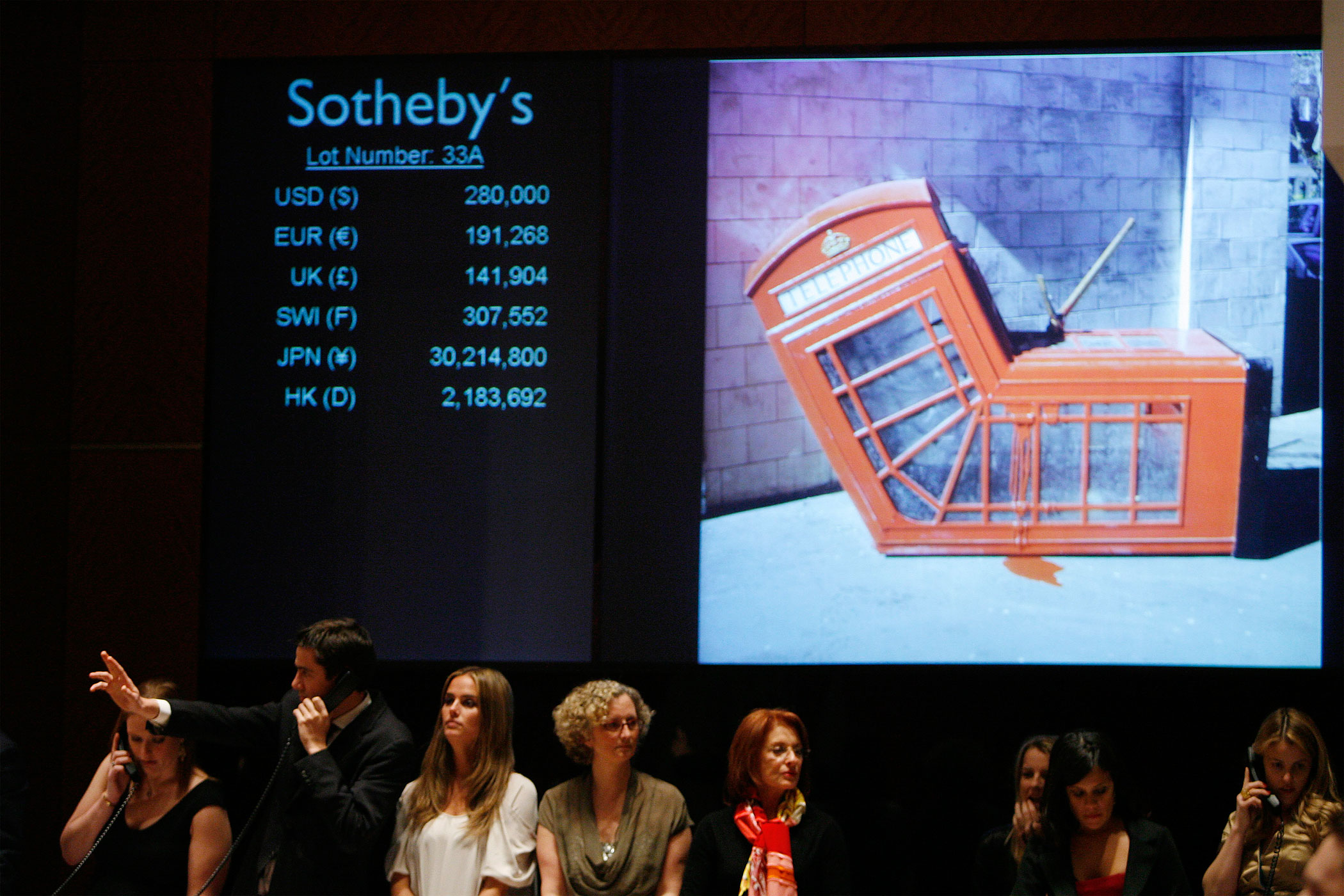 "An employee signals a phone bid on Banksy's ""Vandalised Phone Box"" during Sotheby's ""Red"" benefit auction to raise funds for HIV/AIDS treatment in Africa in New York City on Feb 14, 2008."