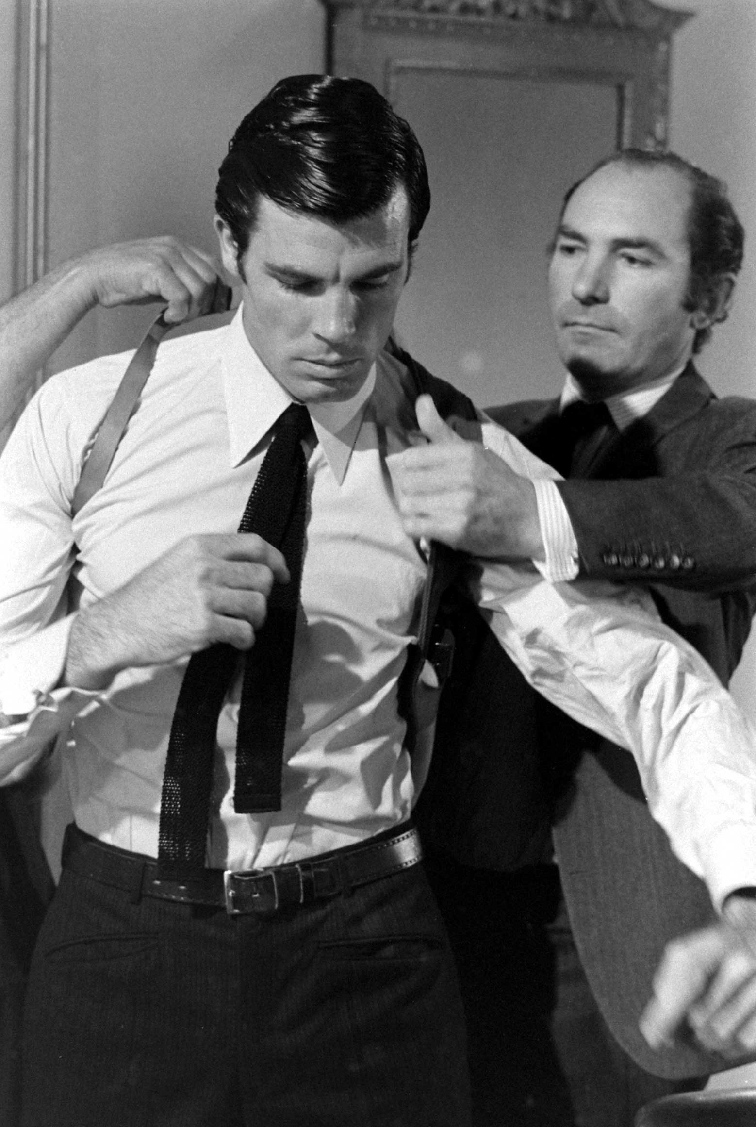 Director Peter R. Hunt helps Robert Campbell get into a shoulder holster, 1967.