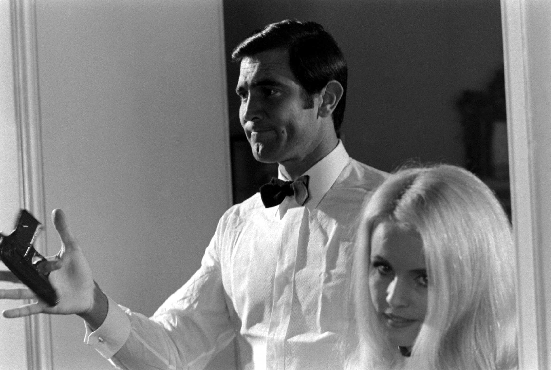 George Lazenby twirls a gun beside potential Bond Girl Marie-France Boyer, 1967.