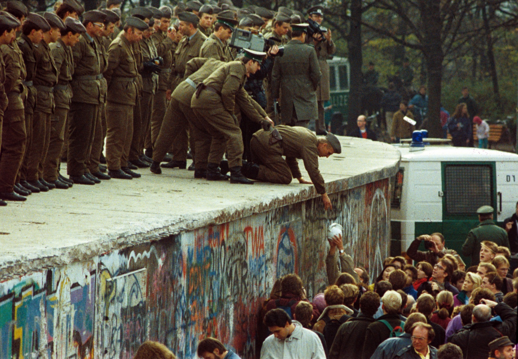 Citizens of West Berlin hand a pot of coffee to GDR border forces on the Berlin Wall on Nov. 11, 1989.
