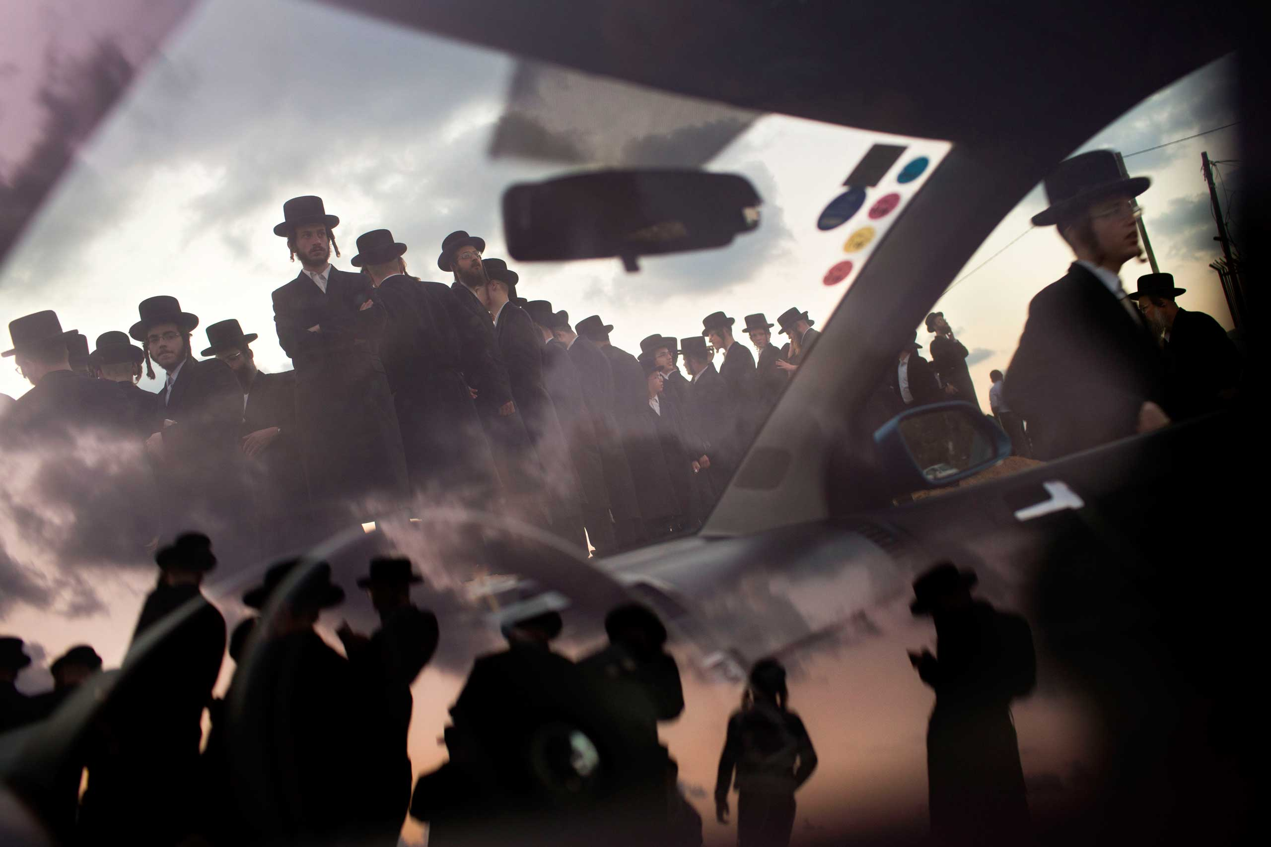 Oct. 2, 2014. Ultra-Orthodox Jews of the Hassidic sect Vizhnitz reflect on a car window as they gather on a hill overlooking the Mediterranean sea as they participate in a Tashlich ceremony in Herzeliya, Israel.