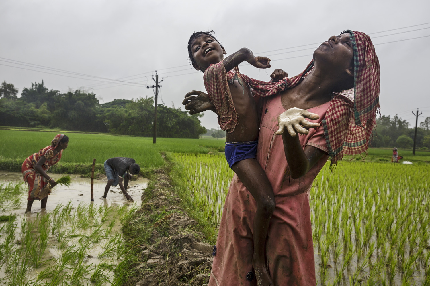Sisters Sonia, right, and Anita Singh, who are both blind, let rain fall on their faces as their parents work nearby