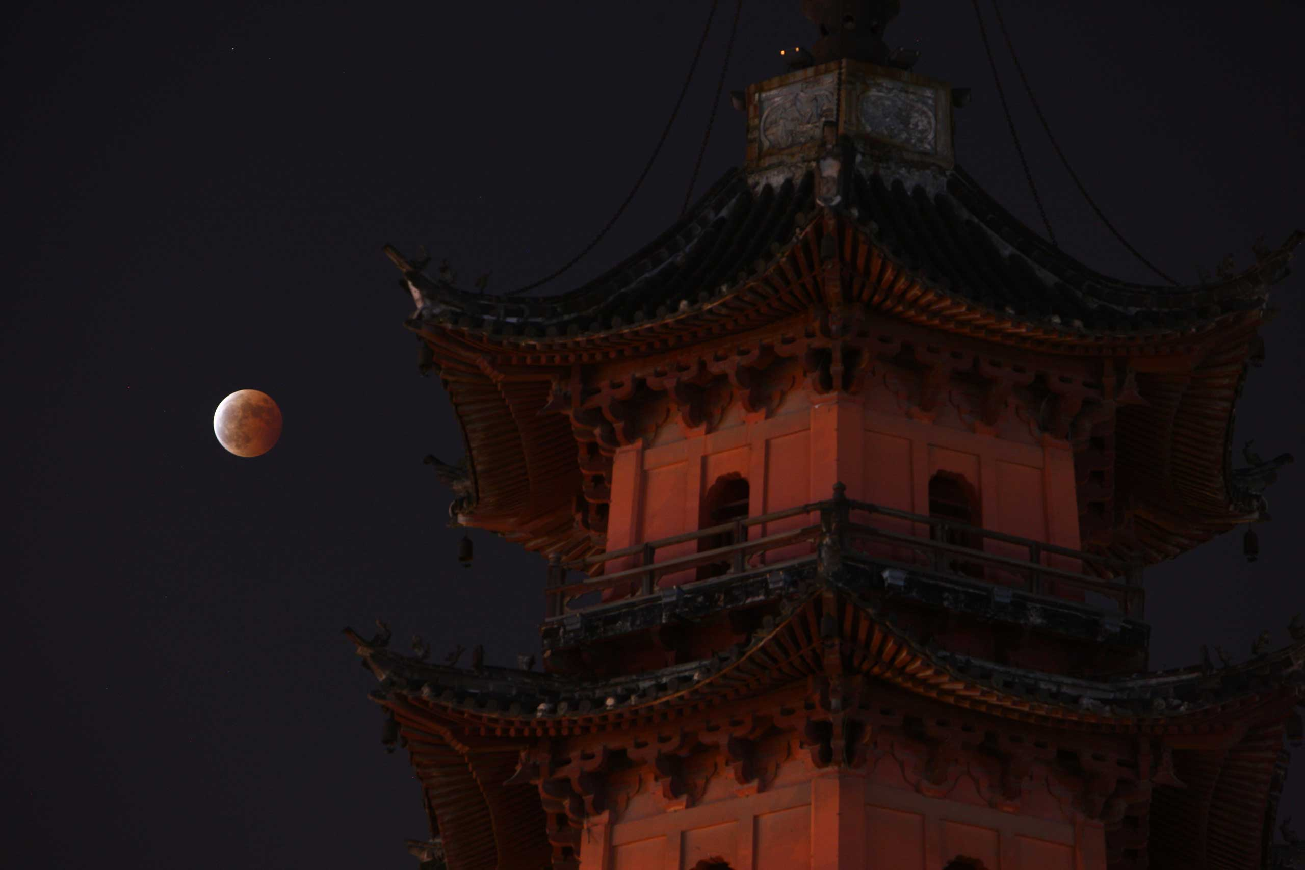 The blood moon resulting from the total lunar eclipse is seen in the sky in Ningbo city, China on Oct. 8, 2014.