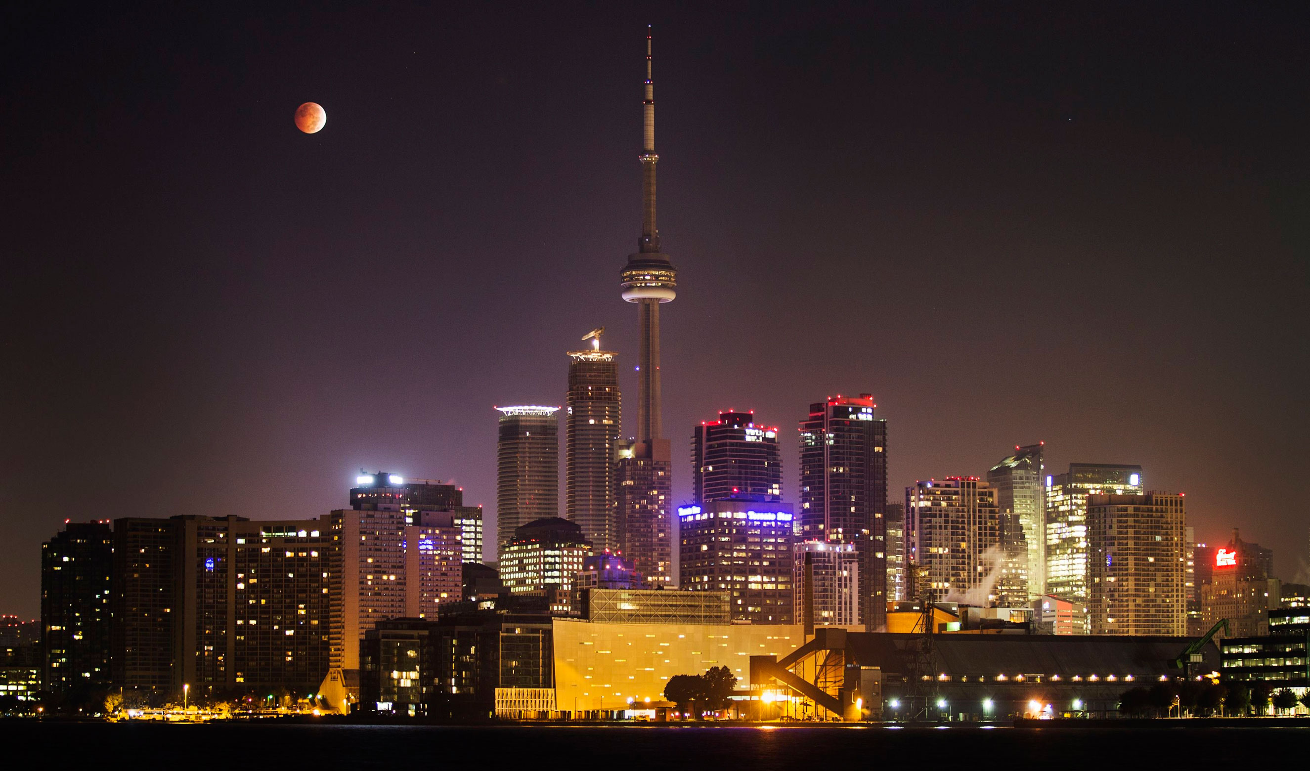 The moon during a total lunar eclipse behind the CN Tower and the skyline of Toronto on Oct. 8, 2014.