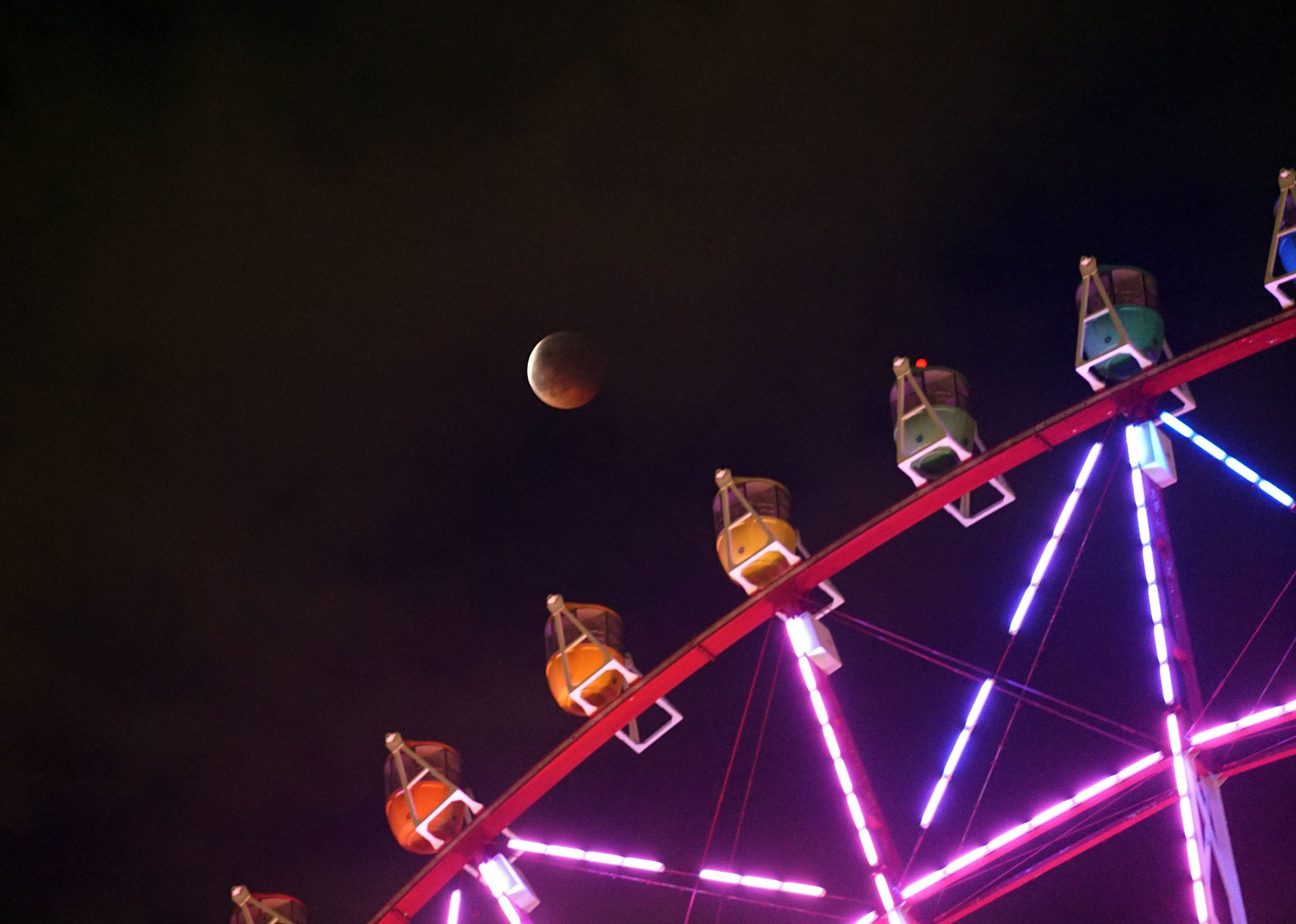 The moon during a total lunar eclipse behind a ferris wheel in Tokyo, on Oct. 8, 2014.