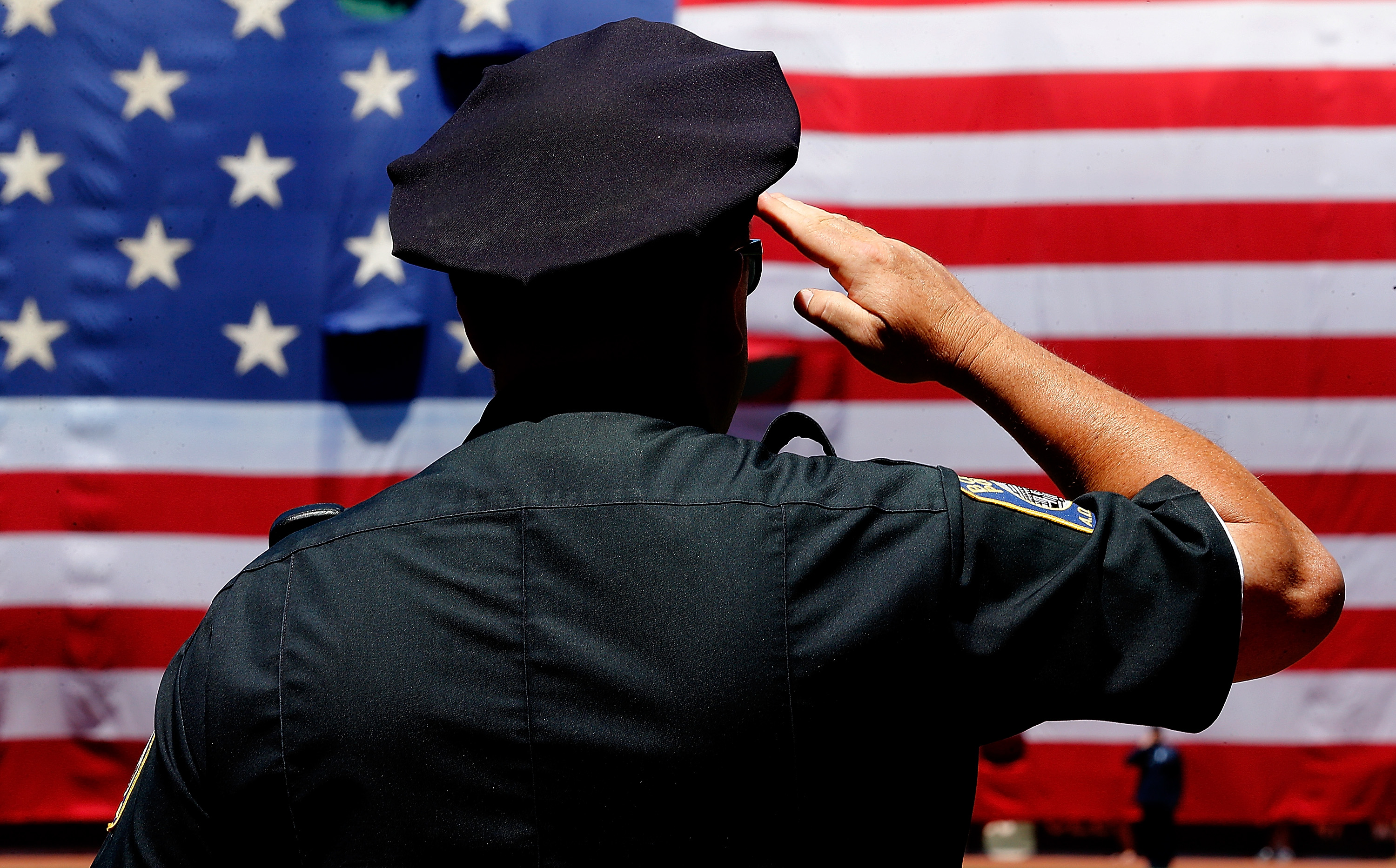 A police officer salutes during the National Anthem before the first game of a doubleheader between the Baltimore Orioles and the Boston Red Sox at Fenway Park on July 5, 2014 in Boston.