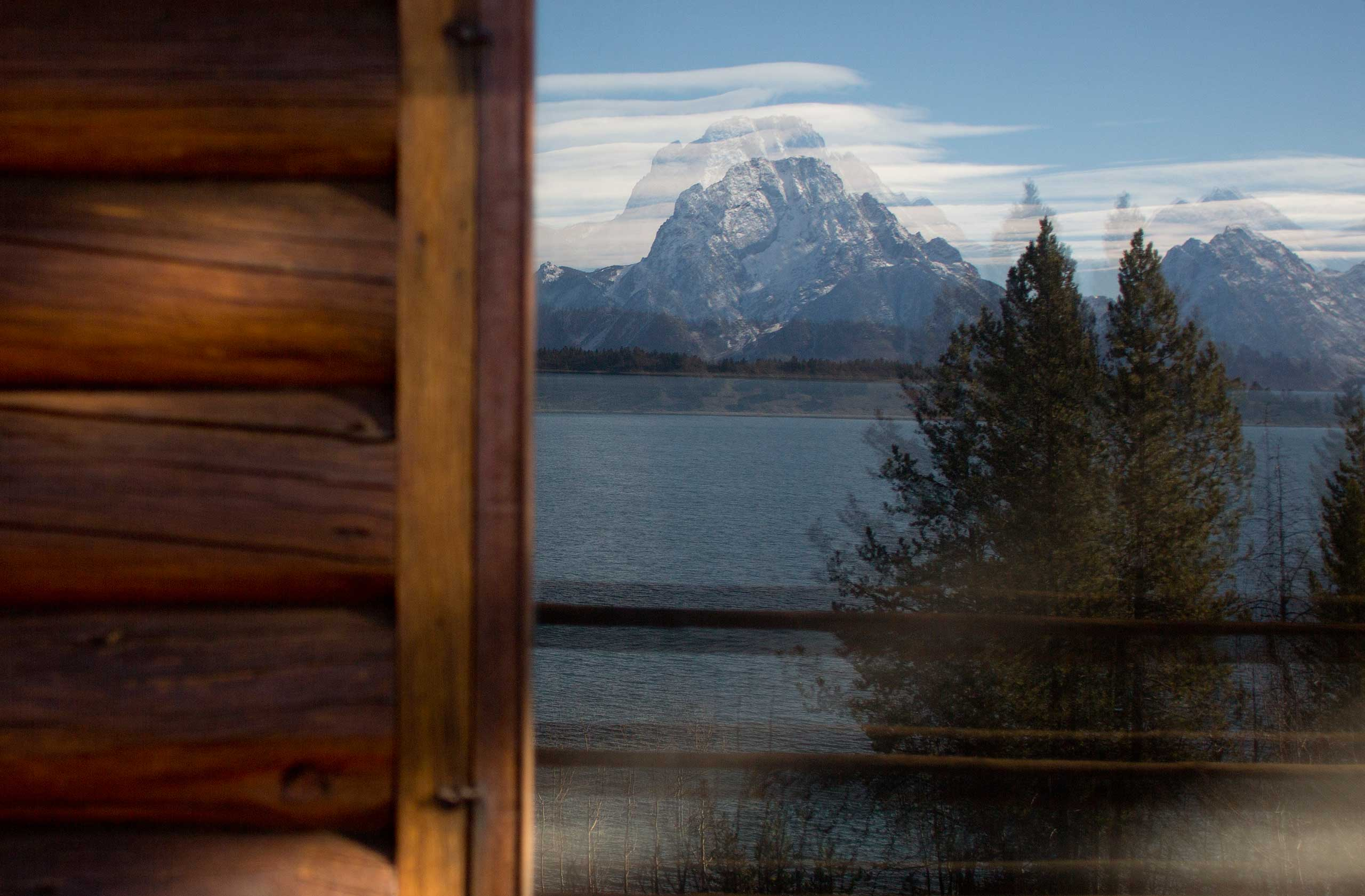 Mountains are reflected in a window of the Brinkerhoff Cabin on the shore of Jackson Lake in Grand Teton National Park outside Jackson, Wyo. on Oct. 28, 2014.