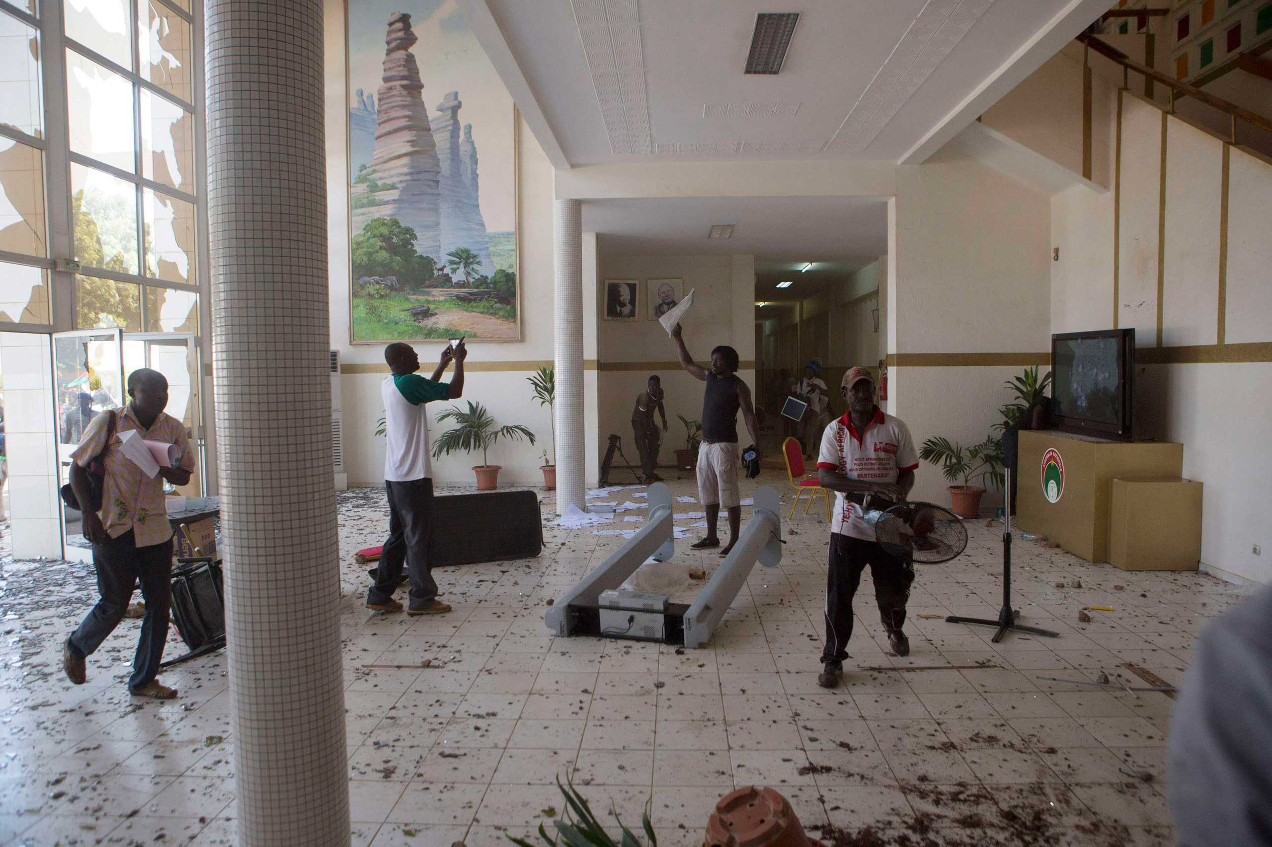 Anti-government protesters loot the parliament building in Ouagadougou, capital of Burkina Faso, Oct. 30, 2014.