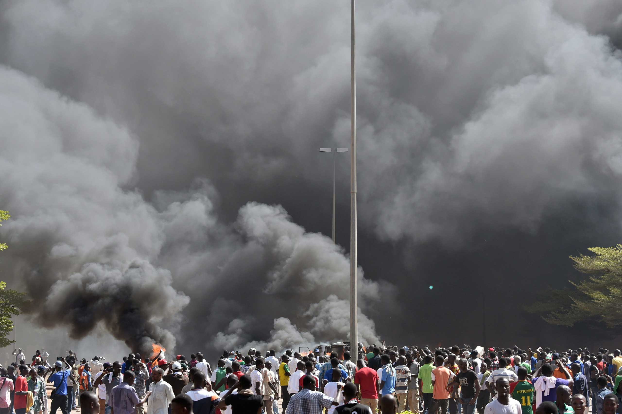 People stand in front of smoke rising from the Burkina Faso's Parliament, where demonstrators put fire on cars parked in a courtyard of the Parliament, on Oct. 30, 2014 in Ouagadougou.