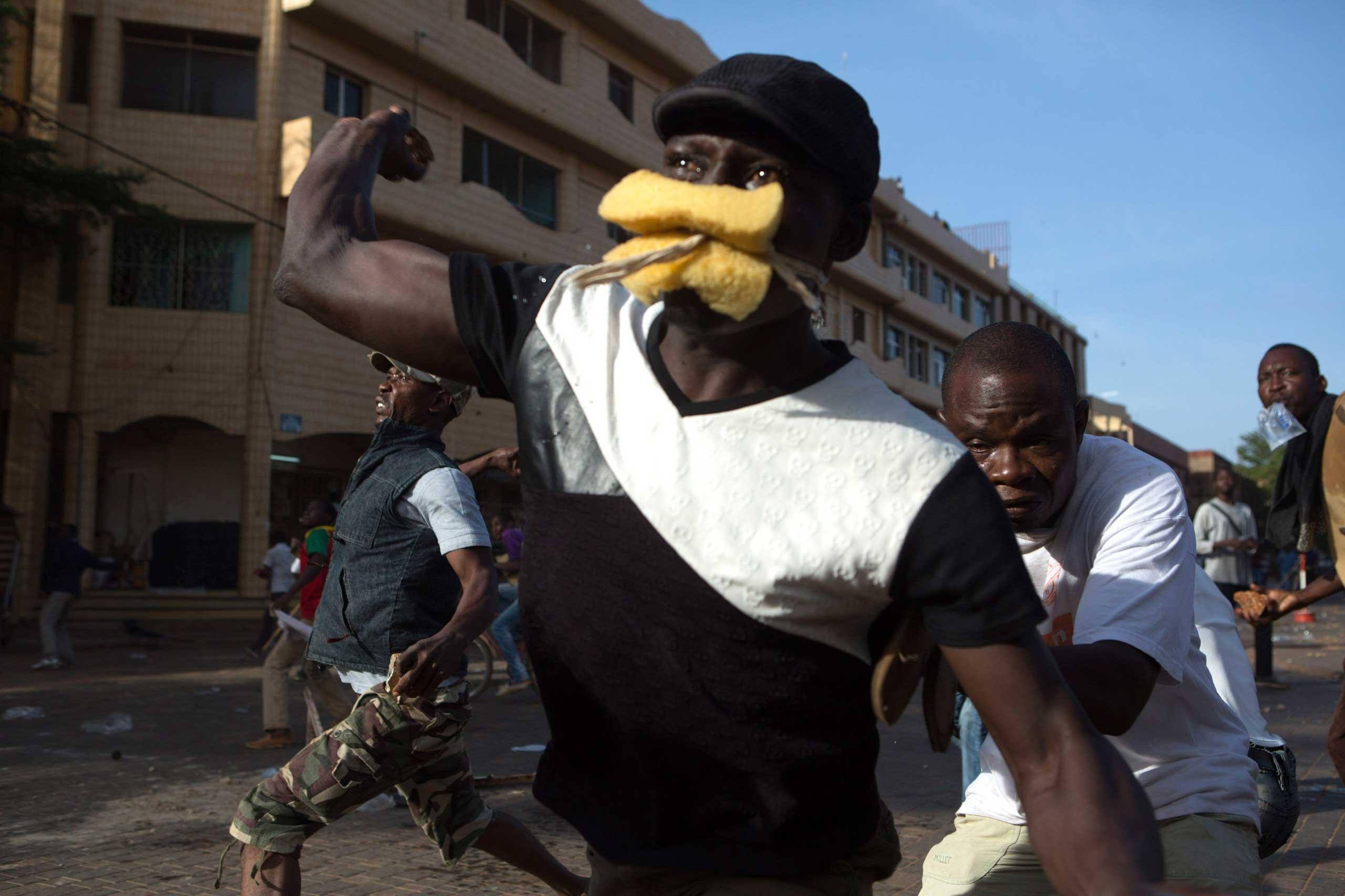 Anti-government protesters throw rocks at police in Ouagadougou, capital of Burkina Faso, Oct. 30, 2014.
