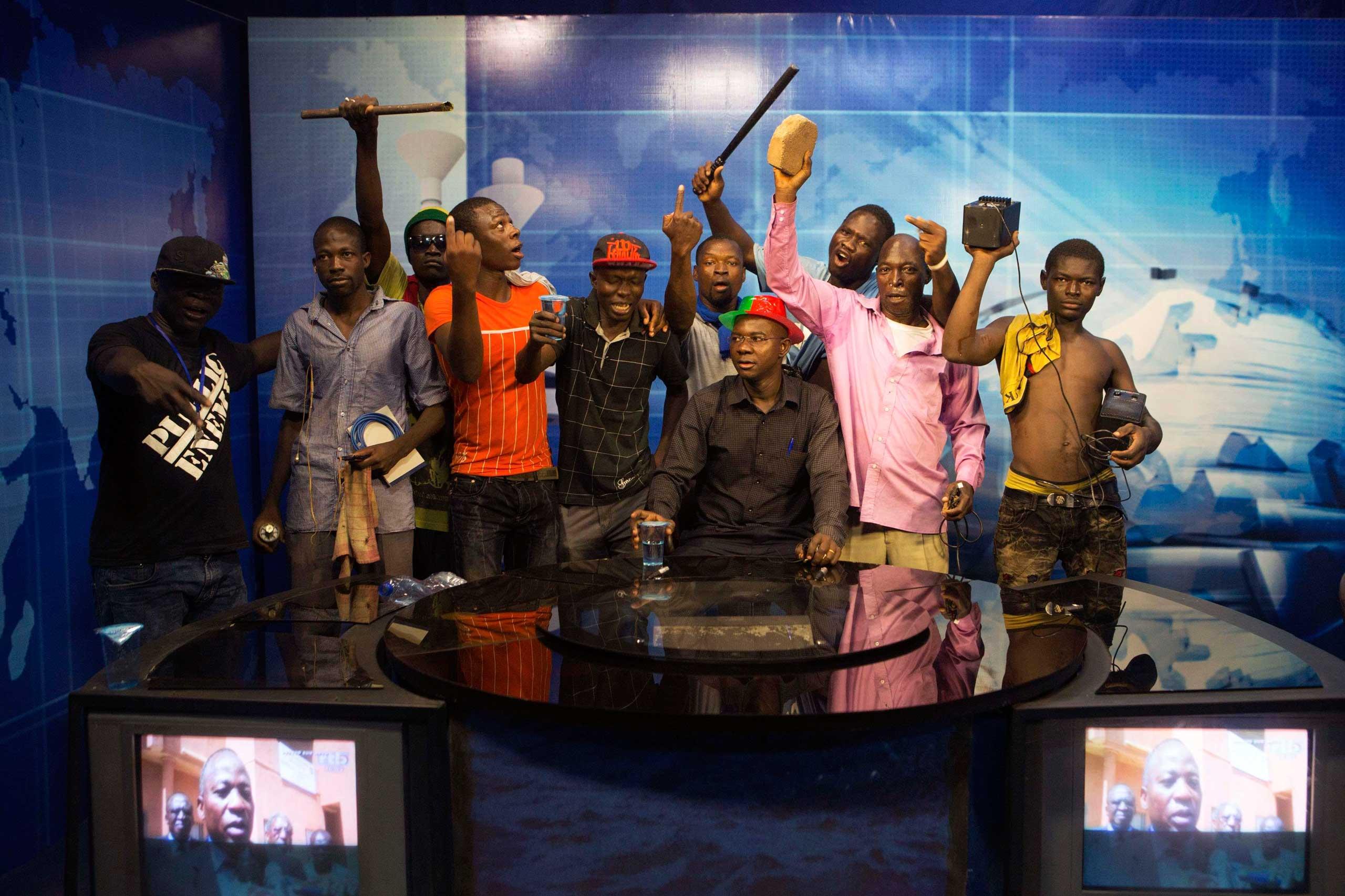 Anti-government protesters take over the state TV podium in Ouagadougou, capital of Burkina Faso, Oct. 30, 2014.