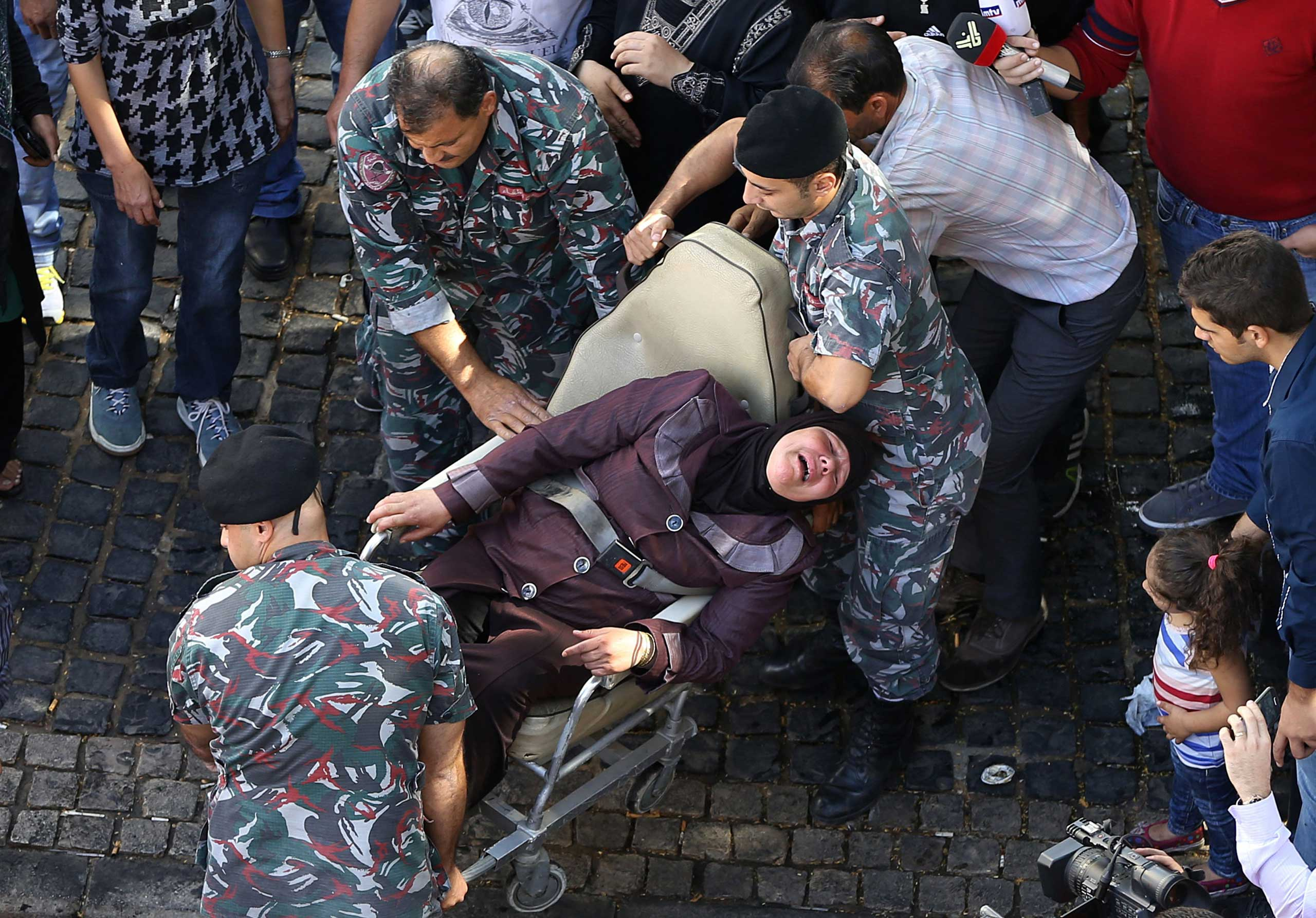 Oct. 30, 2014. A Lebanese mother of a soldier who was kidnapped by Islamic State militants and the Nusra Front, is carried by firefighters after she tried to burn herself with fuel, at an open-ended sit-in by families of kidnapped soldiers and policemen, in downtown Beirut. Militants from the Islamic State (ISIS) extremist group seized around 20 soldiers and policemen after overrunning a Lebanese border town in early August.