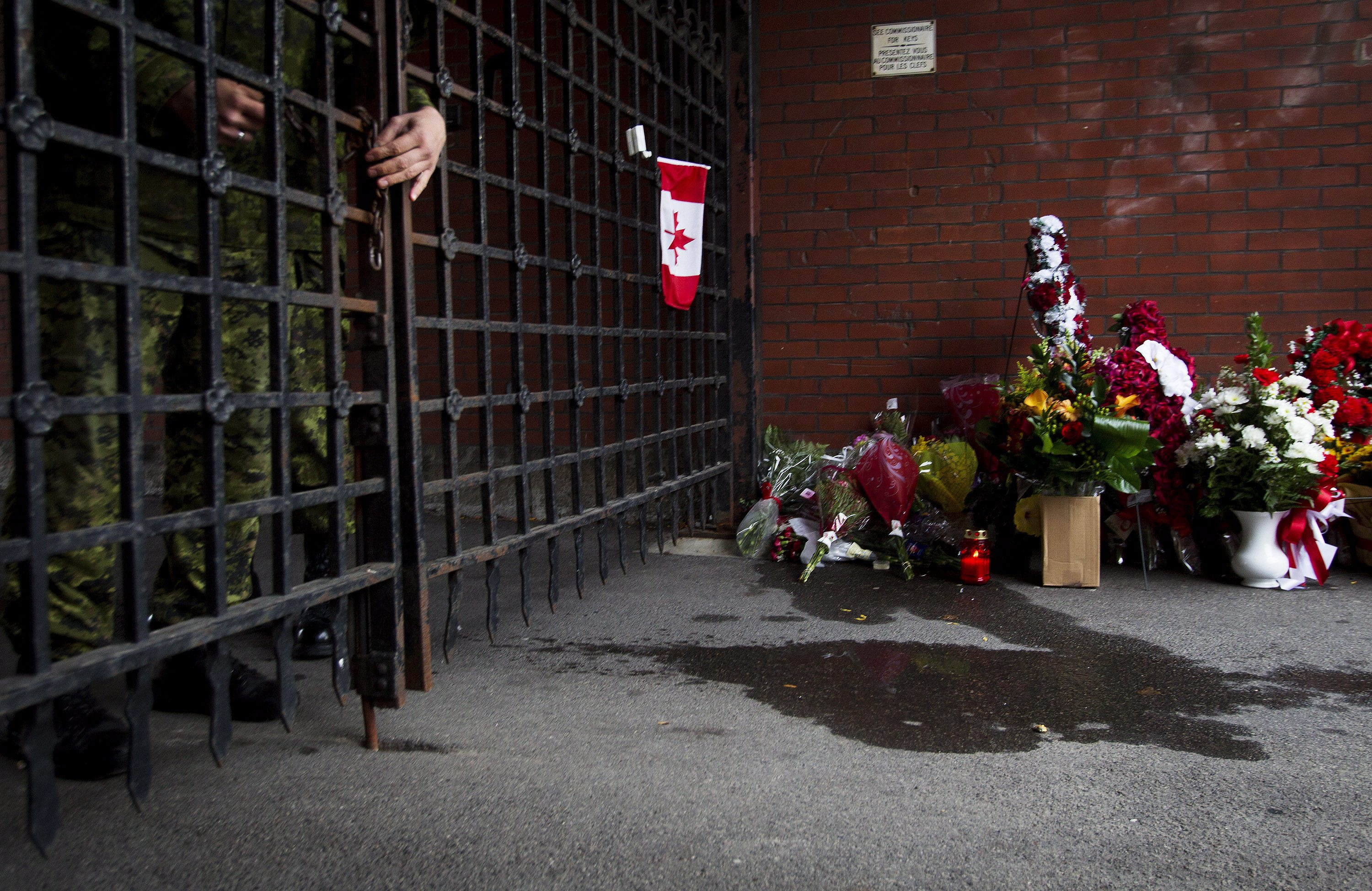 A soldier locks the gates as flowers are placed at a memorial outside the gates of the John Weir Foote Armory, the home of the Argyll and Sutherland Highlanders of Canada in Hamilton, Ontario, on Oct. 22, 2014, in memory of Canadian soldier Nathan Cirillo