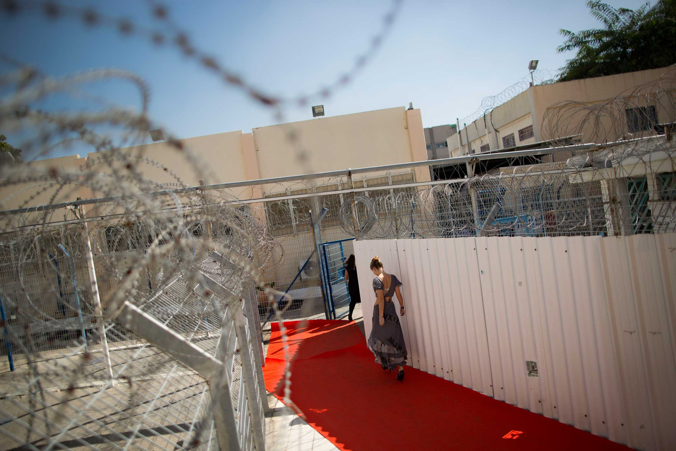 Oct. 27, 2014. A model prepares to walk a runway before a fashion show in Neve Tirza prison in Ramle, central Israel.  Neve Tirza, Israel's only women prison, hosted its first fashion show where models strutted on a red catwalk, showcasing clothes designed and made by inmates.