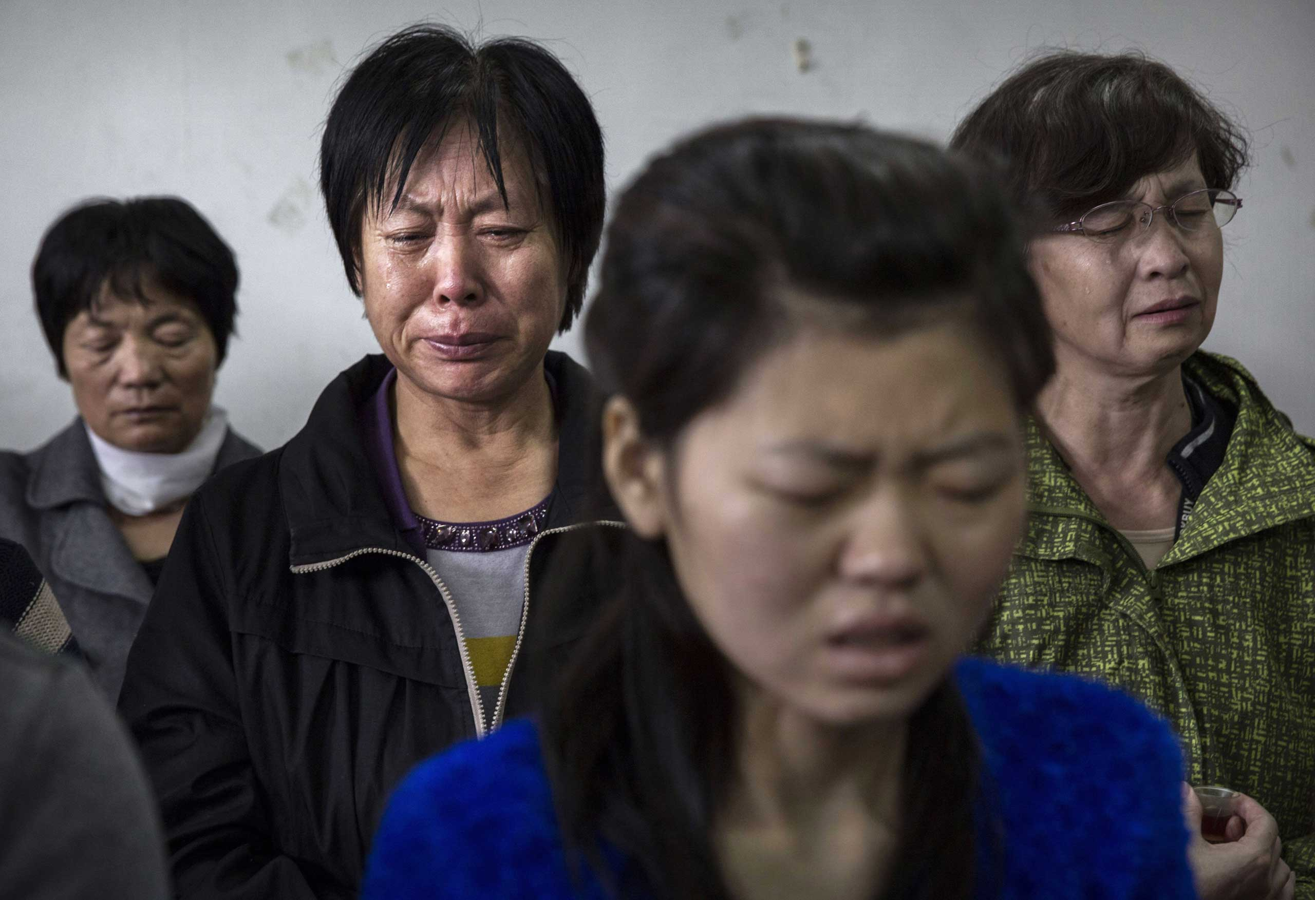 A woman weeps as she and others pray during a service.