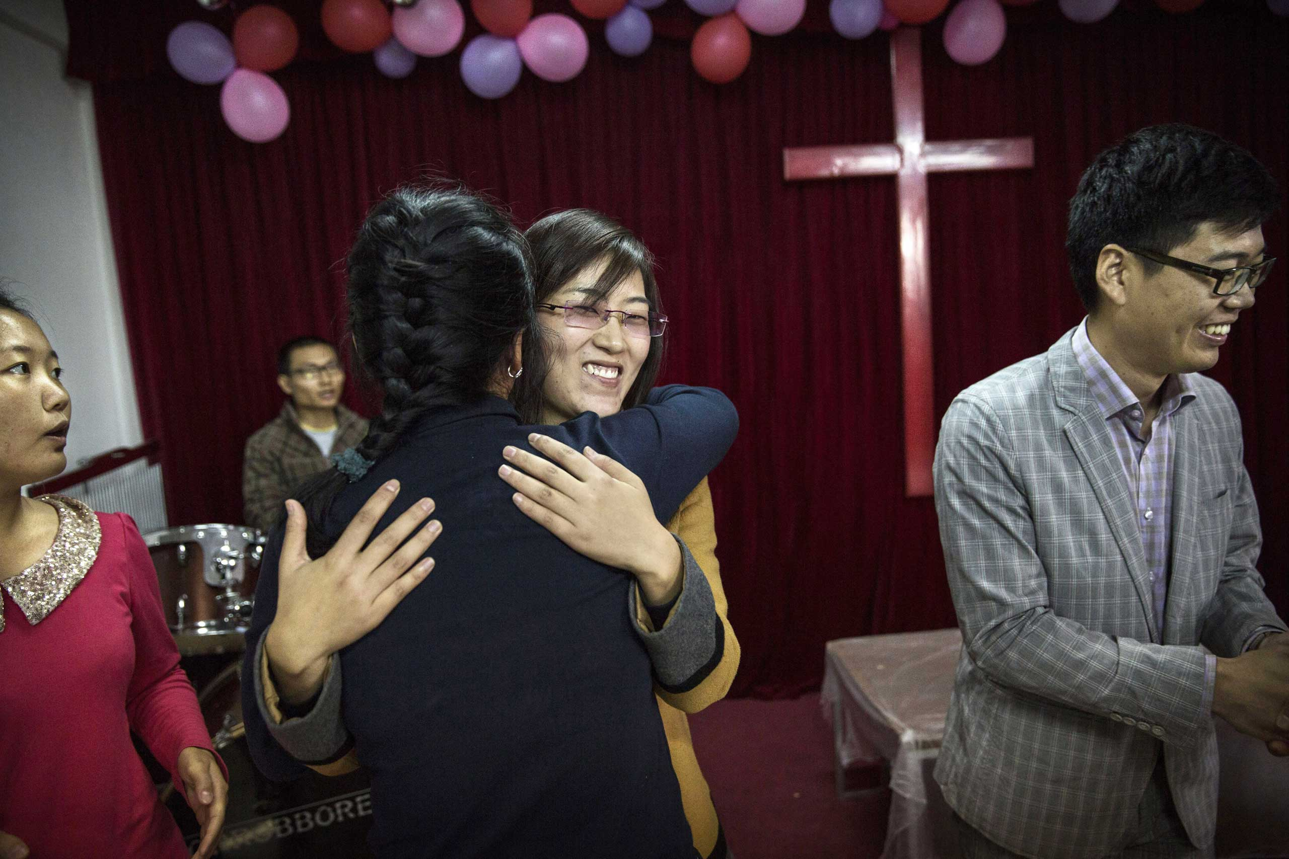 A  woman is embraced by another member of the congregation as she is acknowledged for attending for the first time during a service at an underground independent Protestant Church in Beijing.