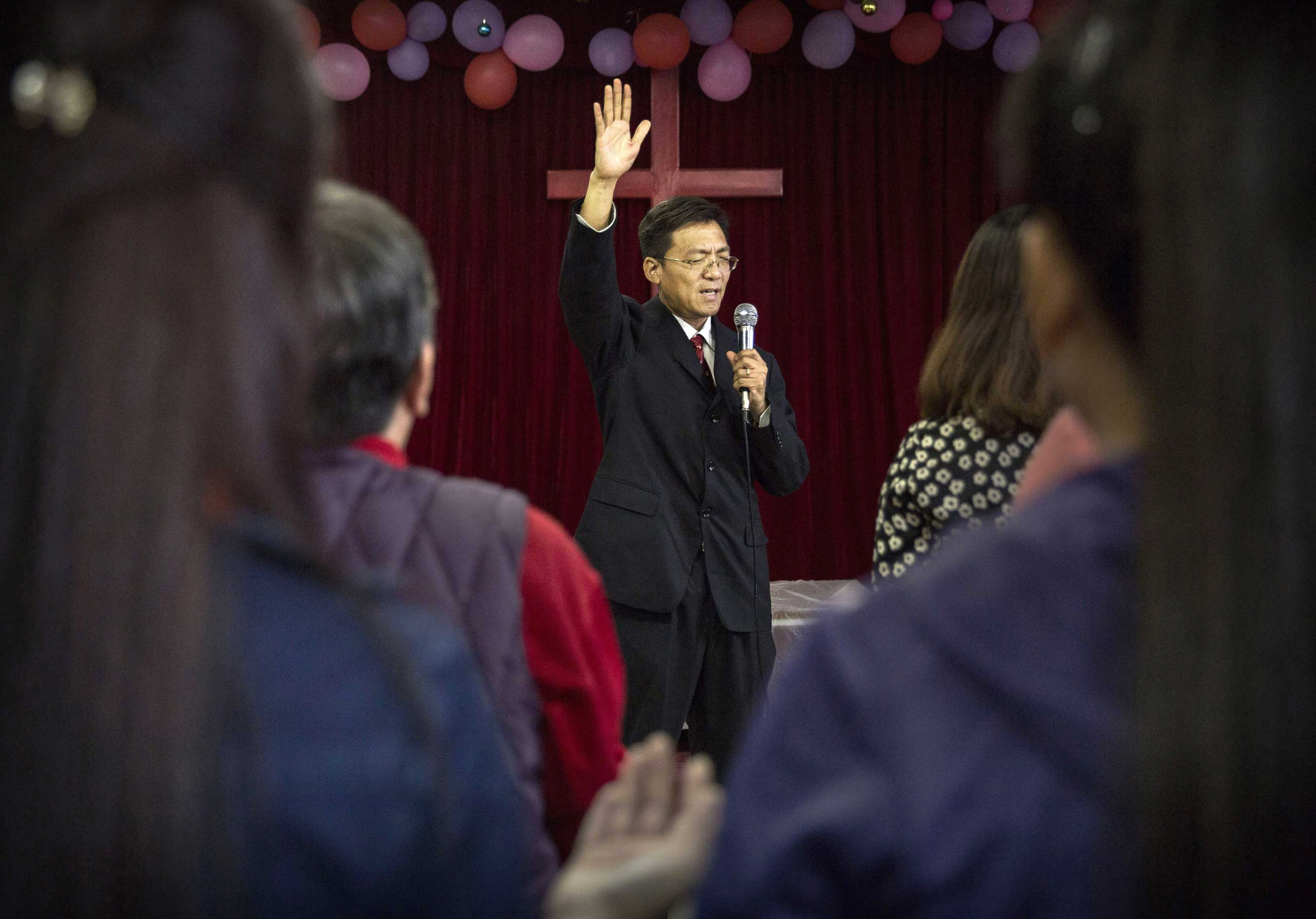 A Chinese Christian pastor leads prayers during a service at an underground independent Protestant Church on Oct. 12, 2014 in Beijing.