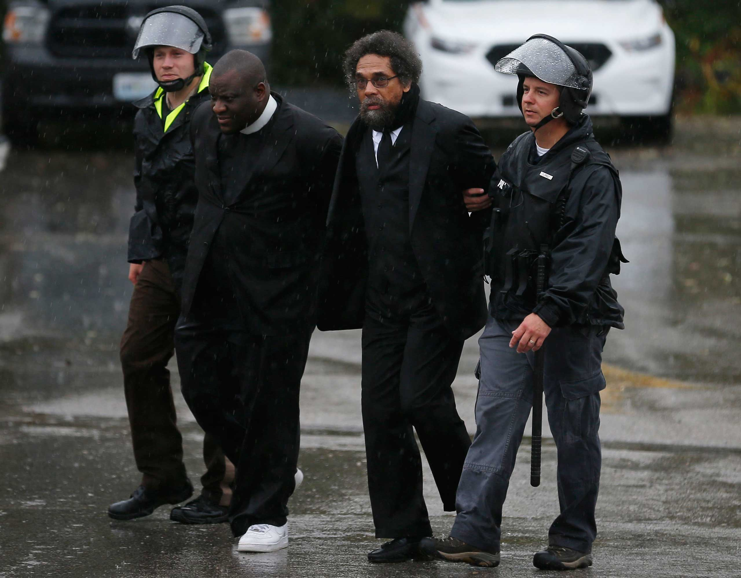 Activist Cornel West (2nd R) is detained by police during a protest at the Ferguson Police Department in Ferguson, Missouri, October 13, 2014.