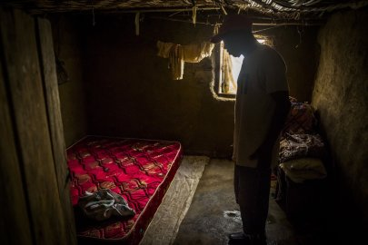 John Yarkpawolo looks over the body of four-day-old Diana Dormeyan, his granddaughter, whose mother died while giving birth to her, at their family home in Gbarnga, Liberia, Oct. 8, 2014.