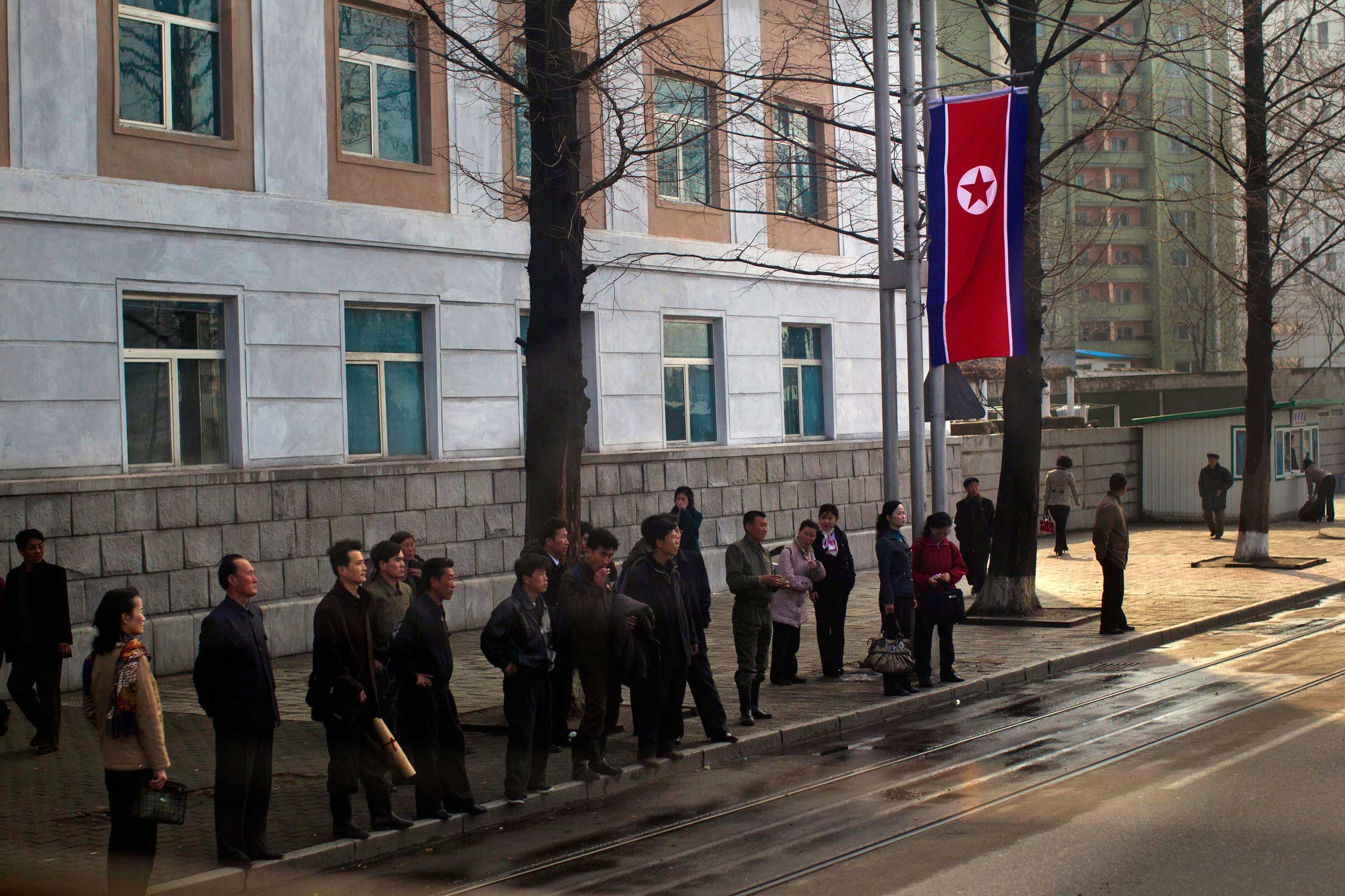April 11, 2012. Under a North Korean flag, residents of Pyongyang wait for public transportation.