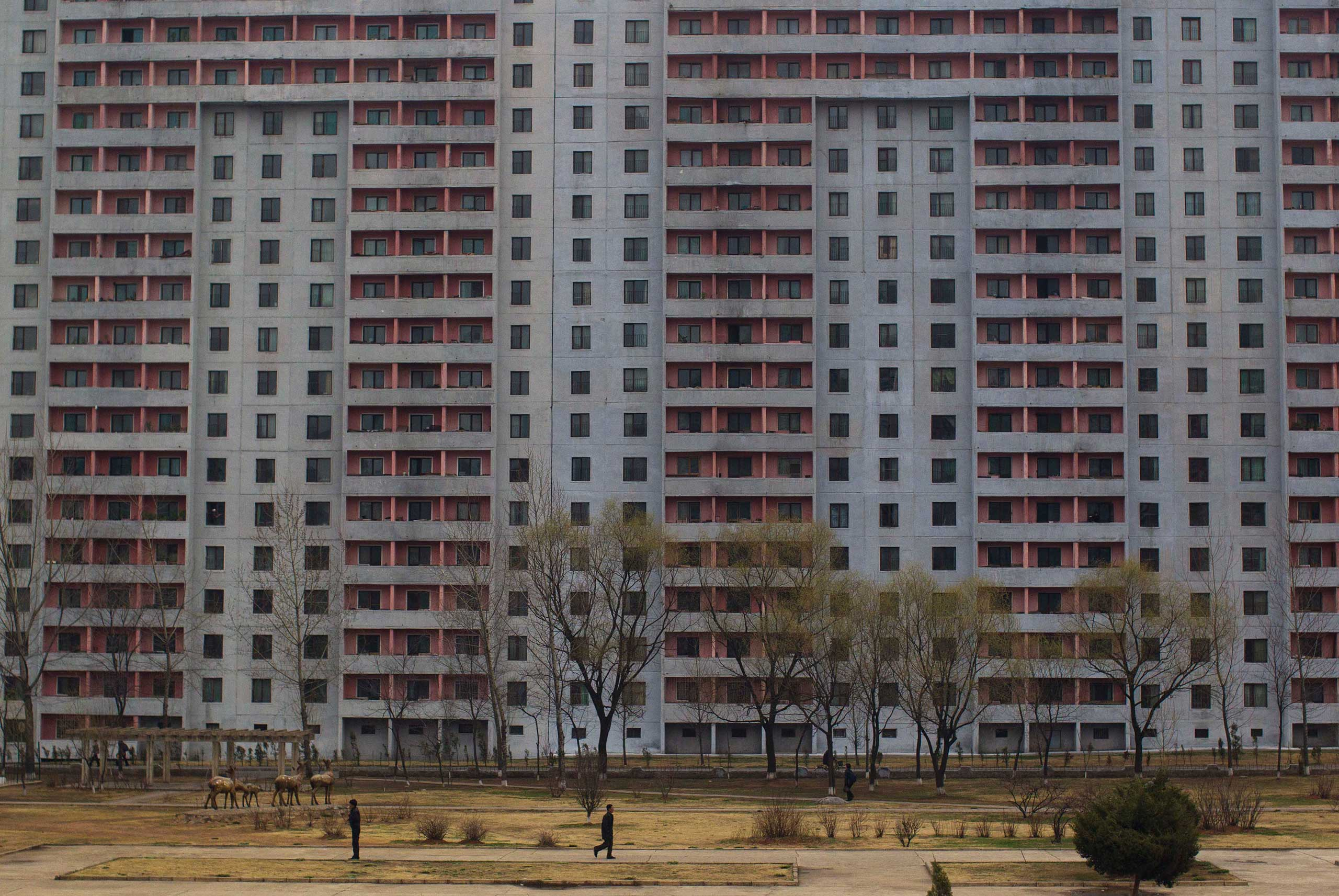 April 12, 2012. A pedestrian walks past a large apartment block in Pyongyang.